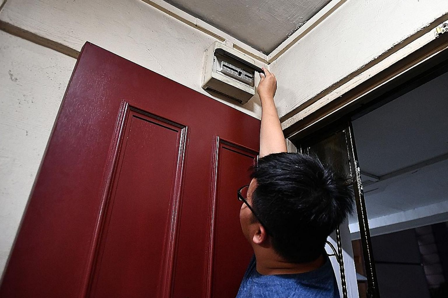 Left: Mr Tan Qi Wei, the brother of 15-year-old Tan Yao Bin who was electrocuted while showering, showing the circuit breaker inside the family's flat yesterday. Three days after his brother's death, the family rewired the whole house and replaced th
