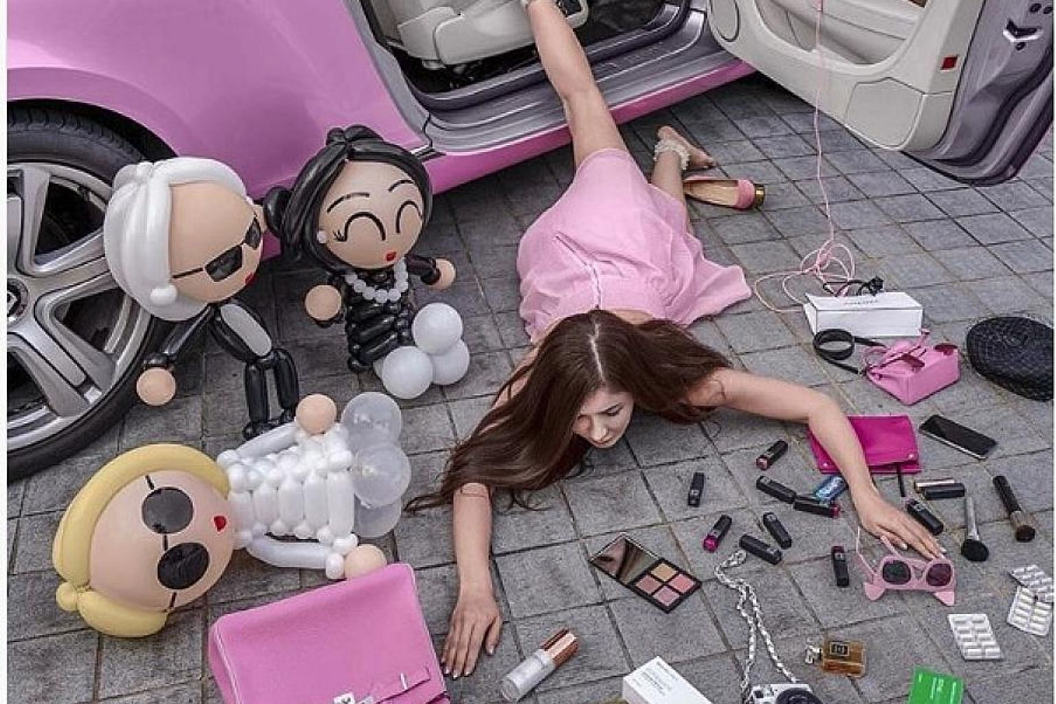 """Singapore socialite Jamie Chua doing the Falling Stars Challenge, which involves people sharing their best """"fake fall"""" pictures on Instagram, surrounded by their expensive possessions."""