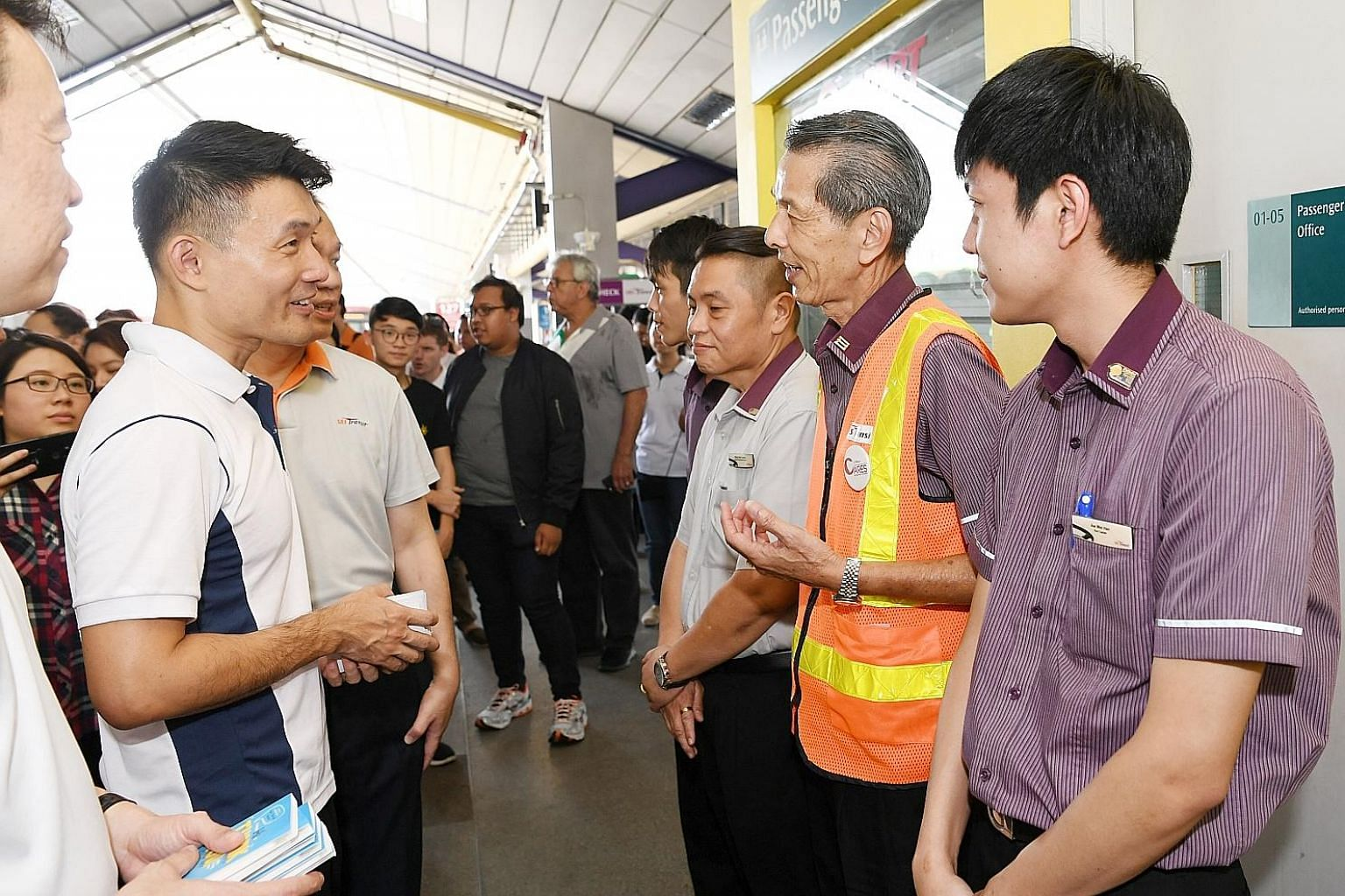 Mr Baey Yam Keng (at far left) speaking to public transport workers from SBS Transit at Tampines Bus Interchange after the launch of the Public Transport Workers' Appreciation Campaign yesterday.
