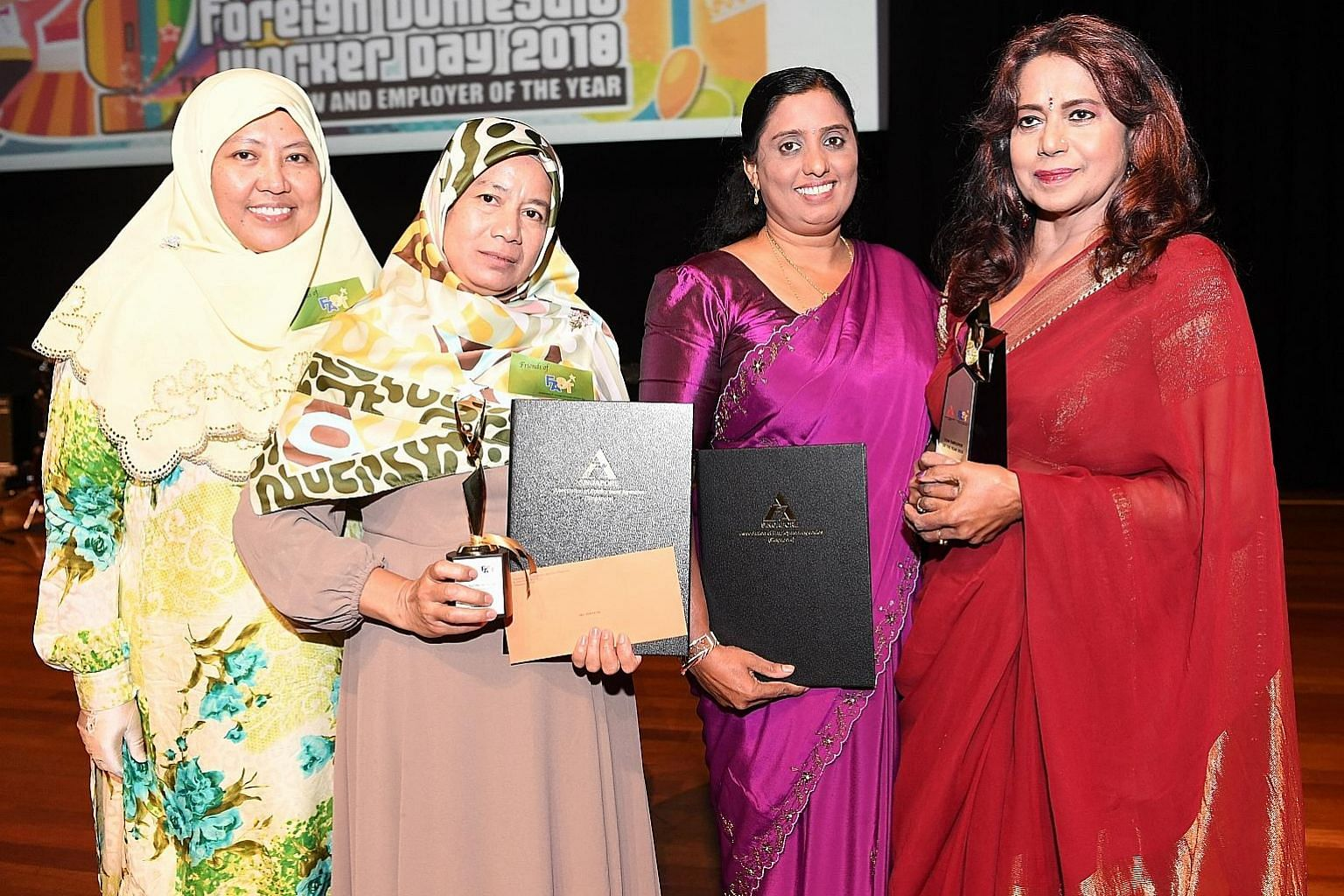 (From left) Employer Umi Saleha with her FDW Sri Wahyuni, who won the FDW of the year award; and FDW Sasenthu Kankanamge Suneetha Iranganie with her employer Bhamah Ramdas, who won the FDW employer of the year award, at yesterday's Foreign Domestic W