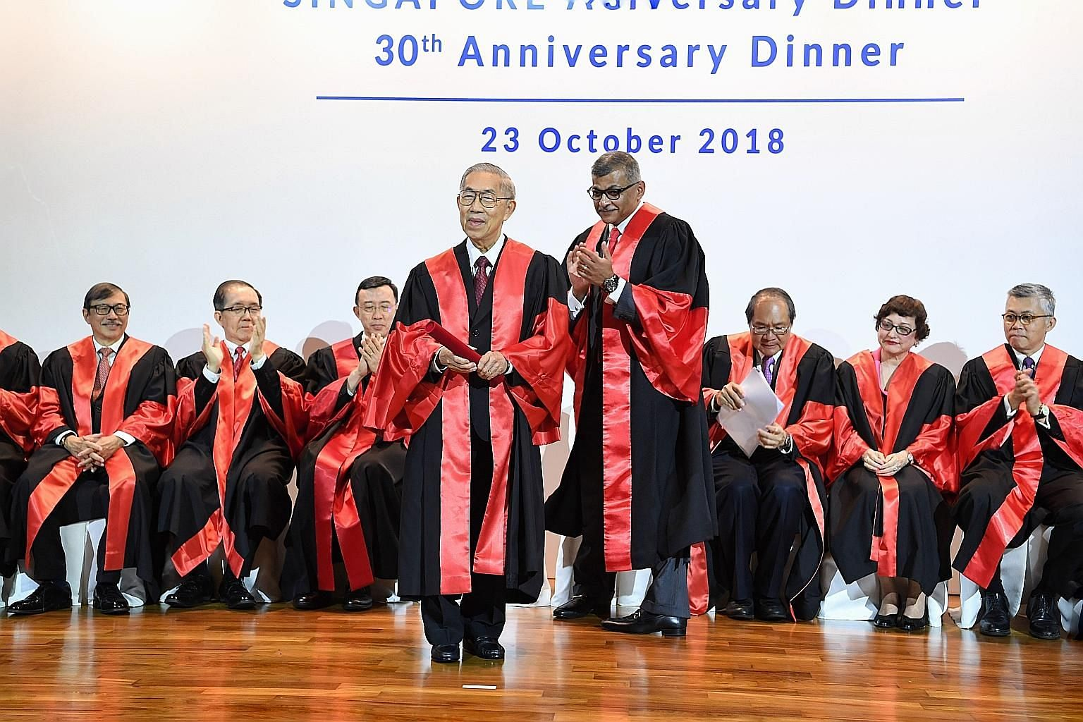 Justice Chao Hick Tin being applauded by Chief Justice Sundaresh Menon and other judges during his conferment ceremony as Honorary Member for Life and Fellow for Life during the Singapore Academy of Law's 30th anniversary dinner last night.