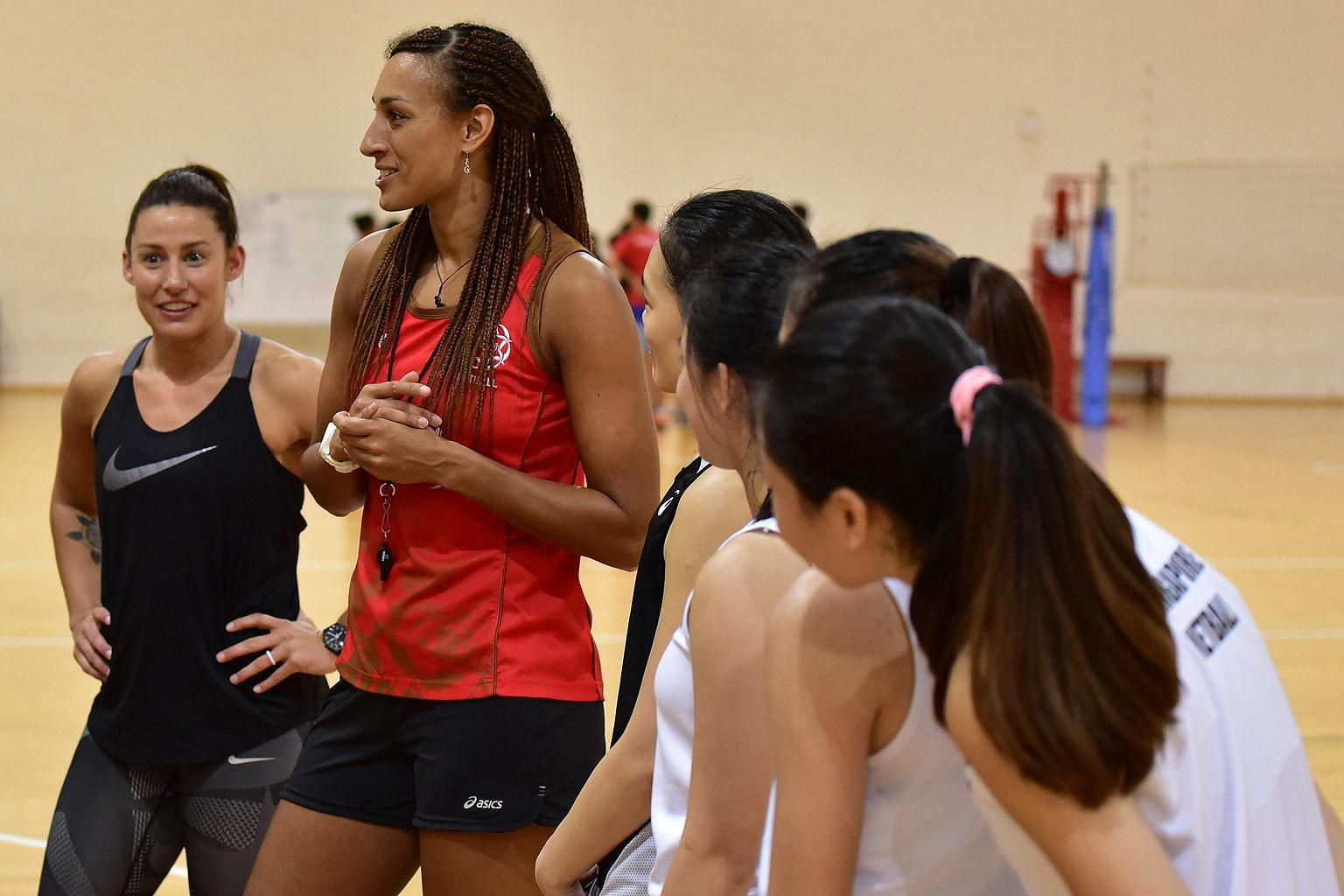 Netball stars Geva Mentor of England (second from left) and Madi Robinson of Australia giving pointers to Singapore's national netballers during a training session at the OCBC Arena last night. The duo will attend the Netball Singapore awards night a