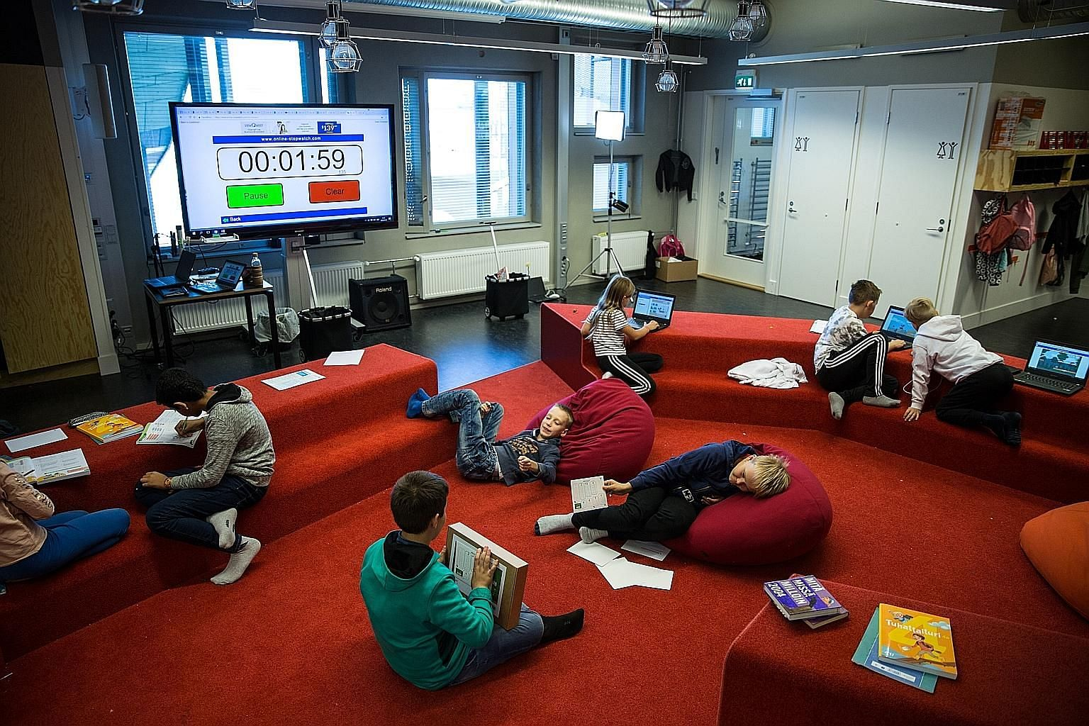 Students from Kalasatama Comprehensive School having a mathematics lesson. Teachers say the open layout and desk-less learning, which more schools in Finland are adopting, help children - both mainstream and special needs - enjoy learning and focus b