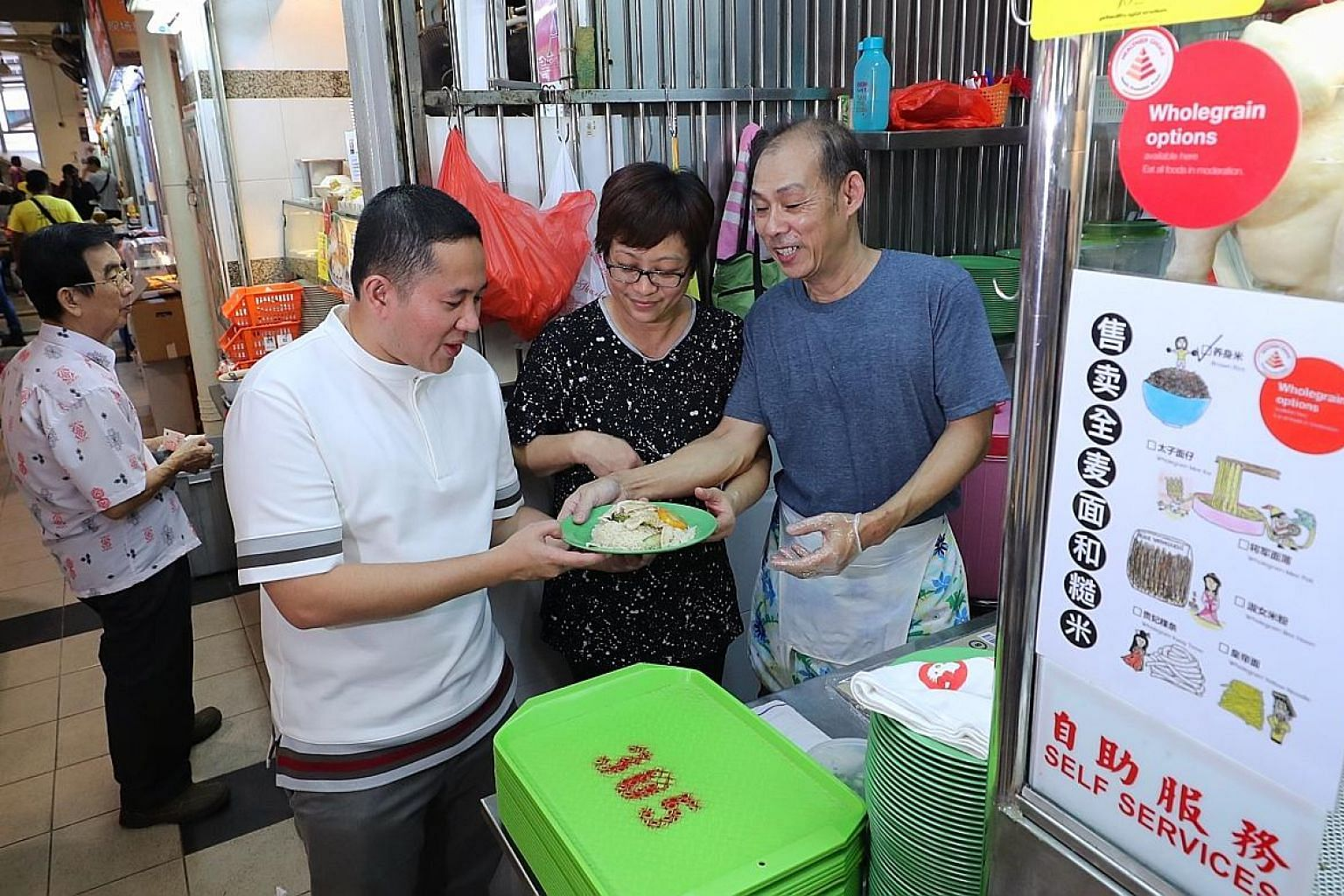 Uncle Jack Hainance Boneless Chicken Rice owner Jack Toh, 54, and his wife Sally Nyo, 52, showing Senior Parliamentary Secretary for Health and Home Affairs Amrin Amin a plate of whole grain chicken rice from their stall. The Health Promotion Board a