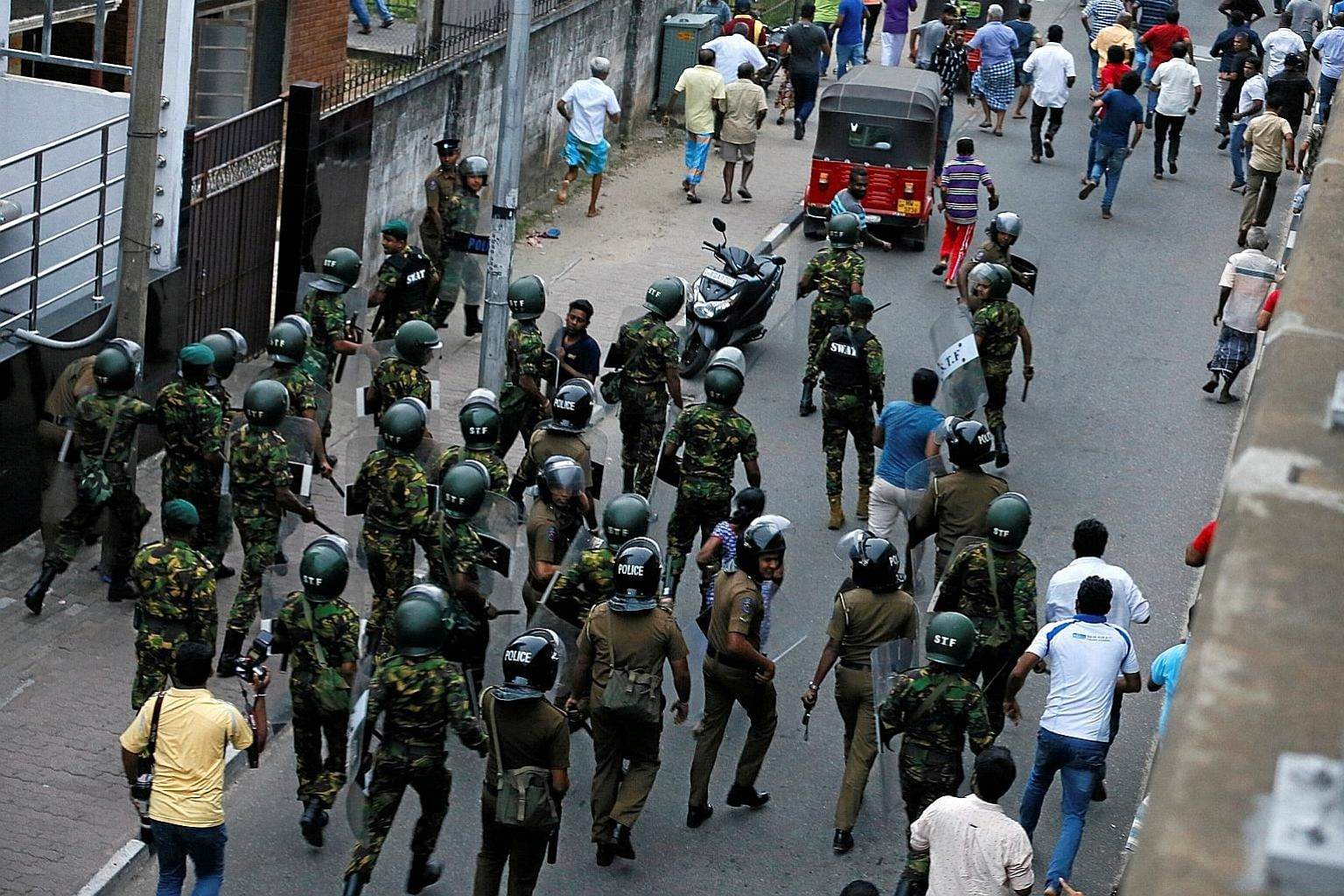 Members of Sri Lanka's Special Task Force and the police chasing away supporters of the country's newly-appointed Prime Minister Mahinda Rajapaksa after a security guard of sacked petroleum minister Arjuna Ranatunga shot and wounded three people in f
