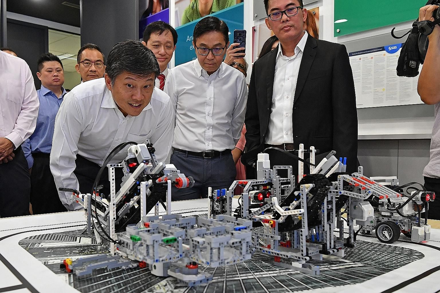 NTUC secretary-general Ng Chee Meng taking a close look at a demonstration of advanced analytics capabilities at the SAS Institute. On his left are Mr Ng Tiong Gee, president of the Tech Talent Assembly; and Mr Randy Goh (in coat), managing director