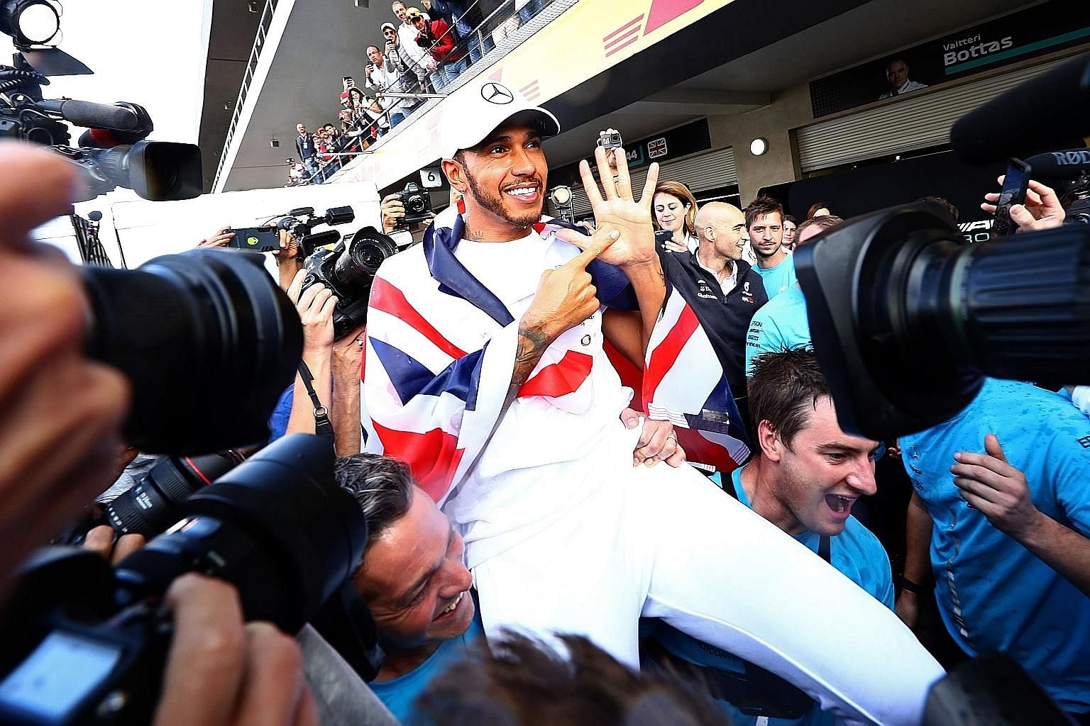 A jubilant Lewis Hamilton after wrapping up his fifth Formula One title at the Mexican Grand Prix on Sunday. He is now two titles away from matching Michael Schumacher.