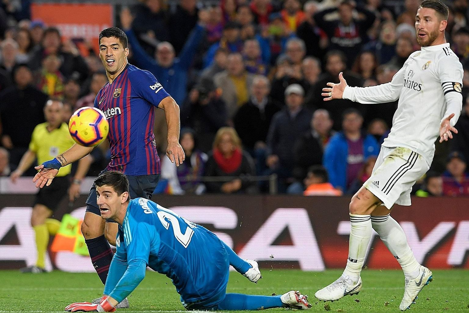 Barcelona striker Luis Suarez dinks the ball over Real Madrid custodian Thibaut Courtois to score his team's fourth goal in the 5-1 thrashing at the Nou Camp on Sunday.