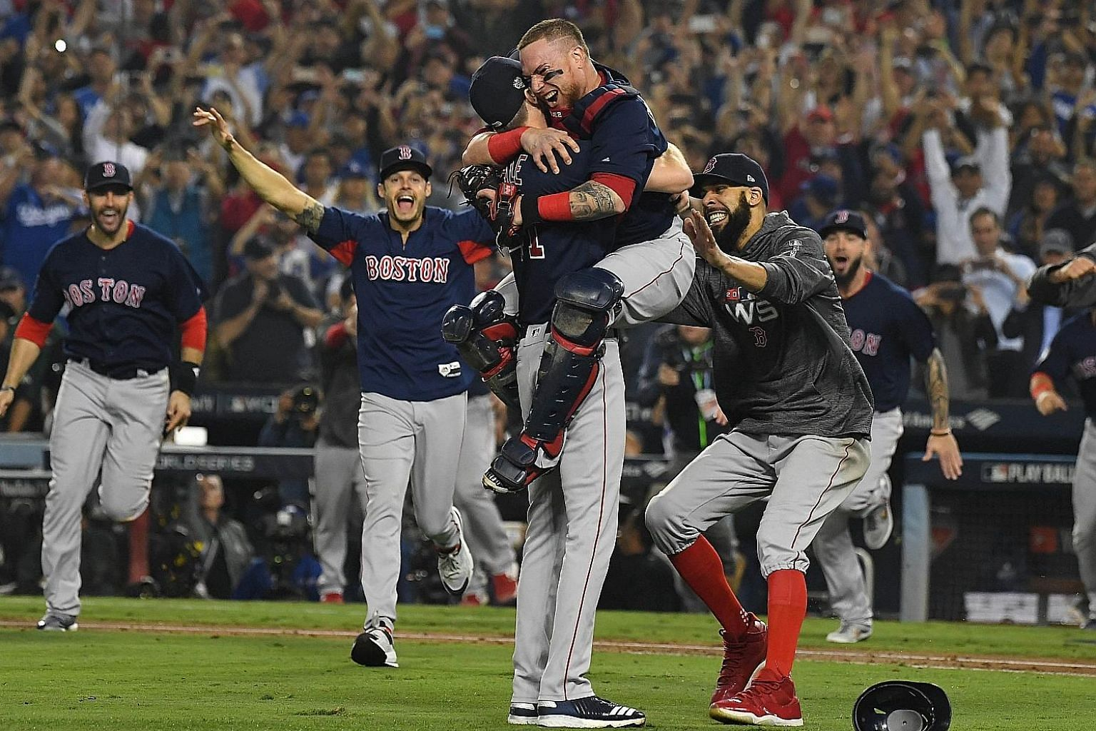 Boston Red Sox players celebrate after defeating the Los Angeles Dodgers 5-1 in Game 5 of the World Series to clinch the title. The Red Sox prevailed by a 4-1 margin in a best-of-seven series. The title triumph was Boston's fourth in 15 years, ninth