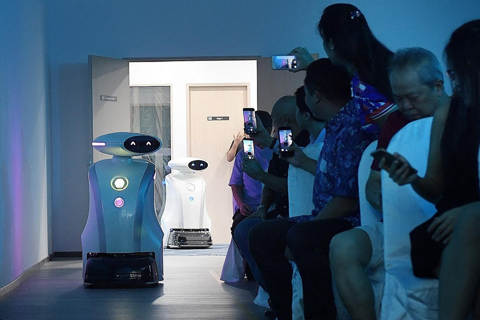 Cleaning robots Ella and Yi Wei at a demonstration yesterday to launch LionsBot International, a Singapore-based cleaning robot venture by founders Dylan Ng, Michelle Seow, and Mohan Rajesh Elara, an assistant professor at the Singapore University of