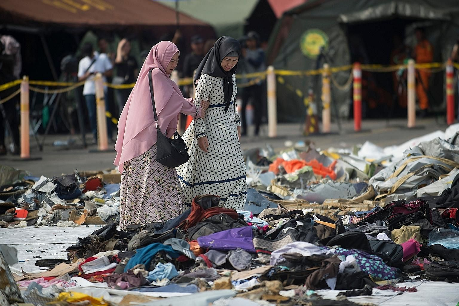 Relatives waiting for news of the forensic investigation at the Police Hospital in Jakarta yesterday. Search and rescue members in Tanjung Priok, with the remains of a body recovered from the crash on Monday. Relatives in Jakarta yesterday trying to