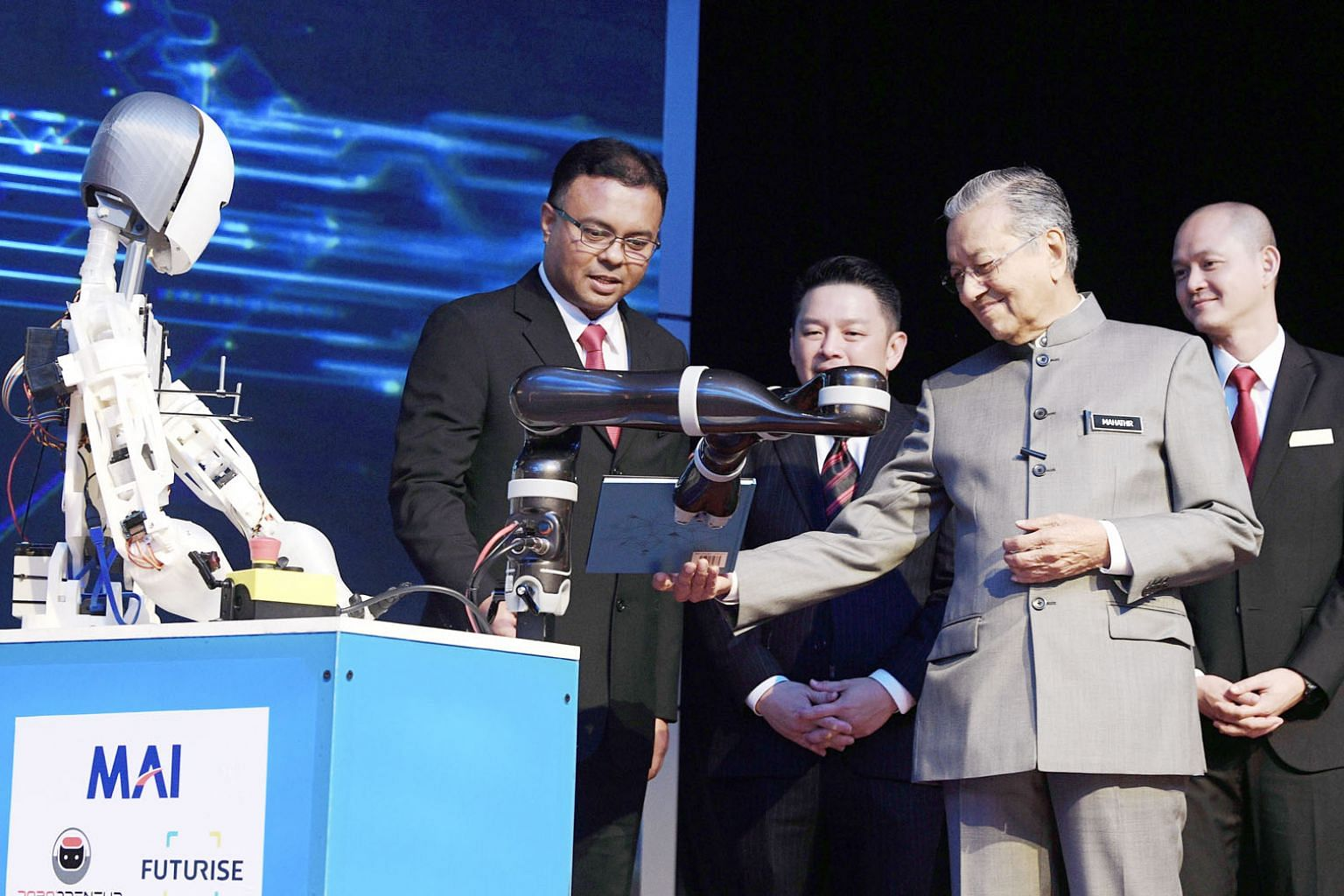 Tun Dr Mahathir Mohamad receiving the National Policy on Industry 4.0 book from a robotic arm at the launch event yesterday. With him are International Trade and Industry Minister Darell Leiking (third from right) and Deputy Minister Ong Kian Ming (r