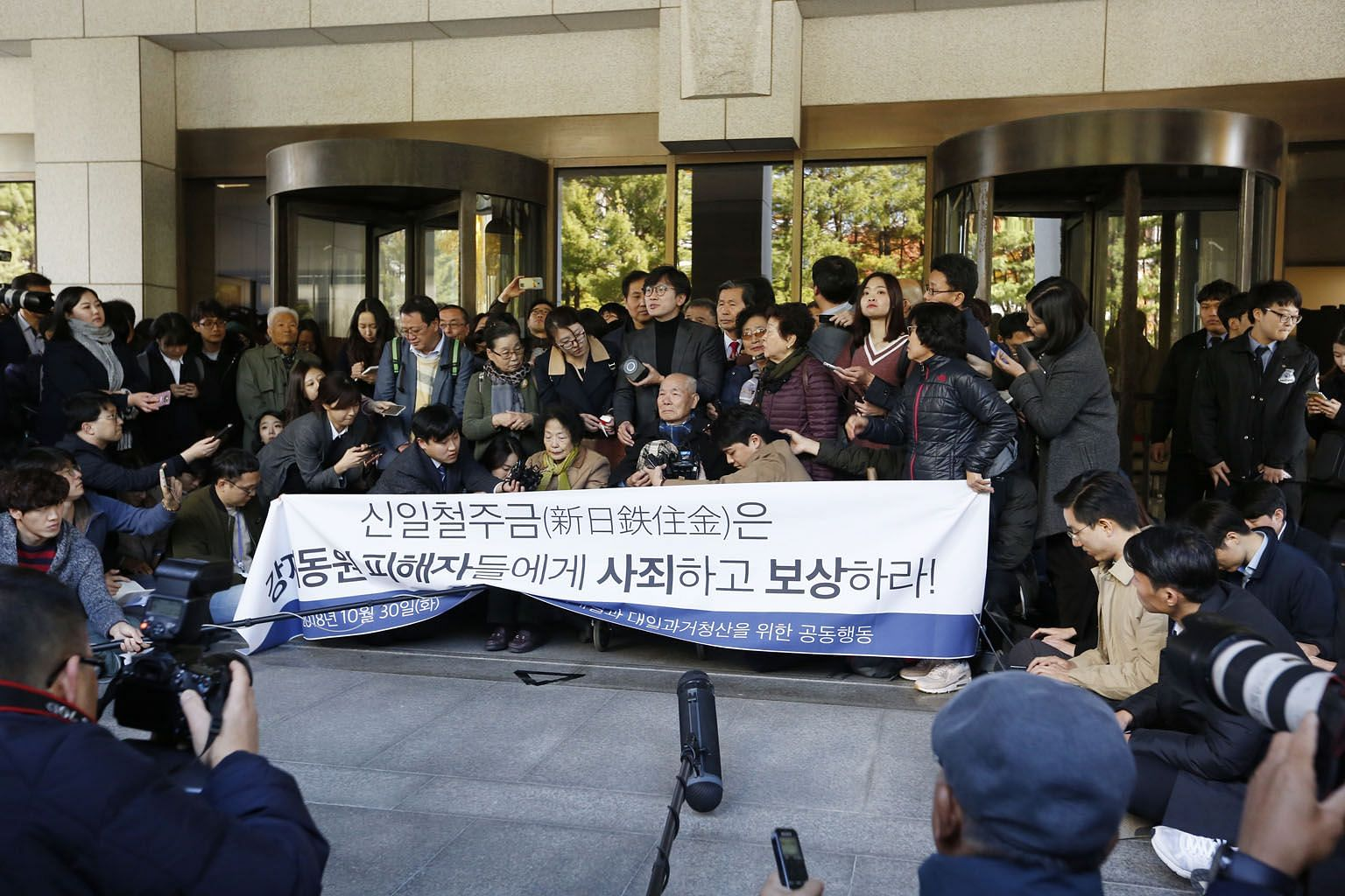Mr Lee Chun-sik (centre, seated), 94, who was a victim of forced labour during the Japanese colonial rule of the Korean Peninsula from 1910 to 1945, at the Supreme Court on Tuesday. The court has ordered Japan's Nippon Steel and Sumitomo Metal Corpor