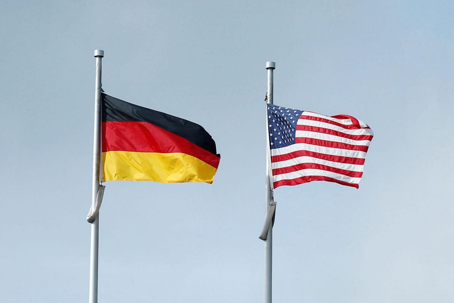 The German (left) and US flags. Chancellor Angela Merkel and President Donald Trump are not just miles, but probably a whole universe, apart.