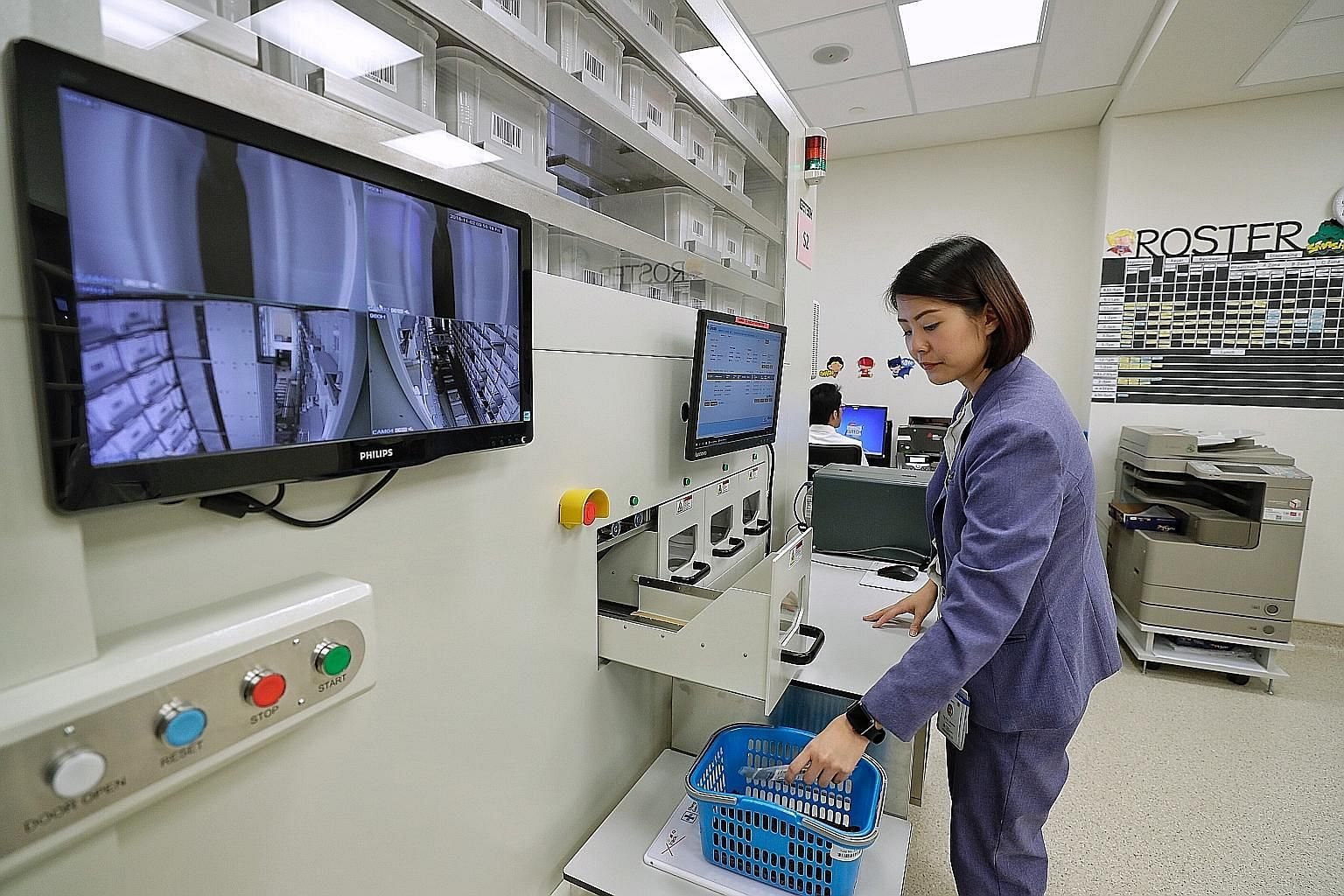 Right: A pharmacist picking up medicine from the outpatient pharmacy automation system (Opas). With Opas, over 50 per cent of same-day consultation patients receive their medication within 10 minutes, and that is twice as many patients as before. Lef