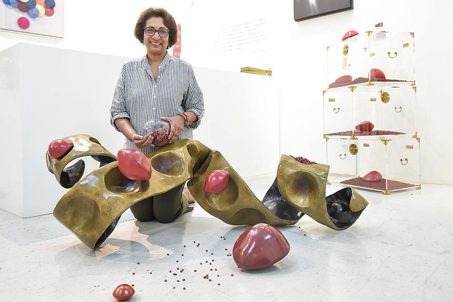 KUMARI NAHAPPAN, who has collected more than 18 million saga seeds over two decades. With her is her current work, in which a larger-than-life sculpture of an exploding saga seed pod will sit in a sea of scattered seeds