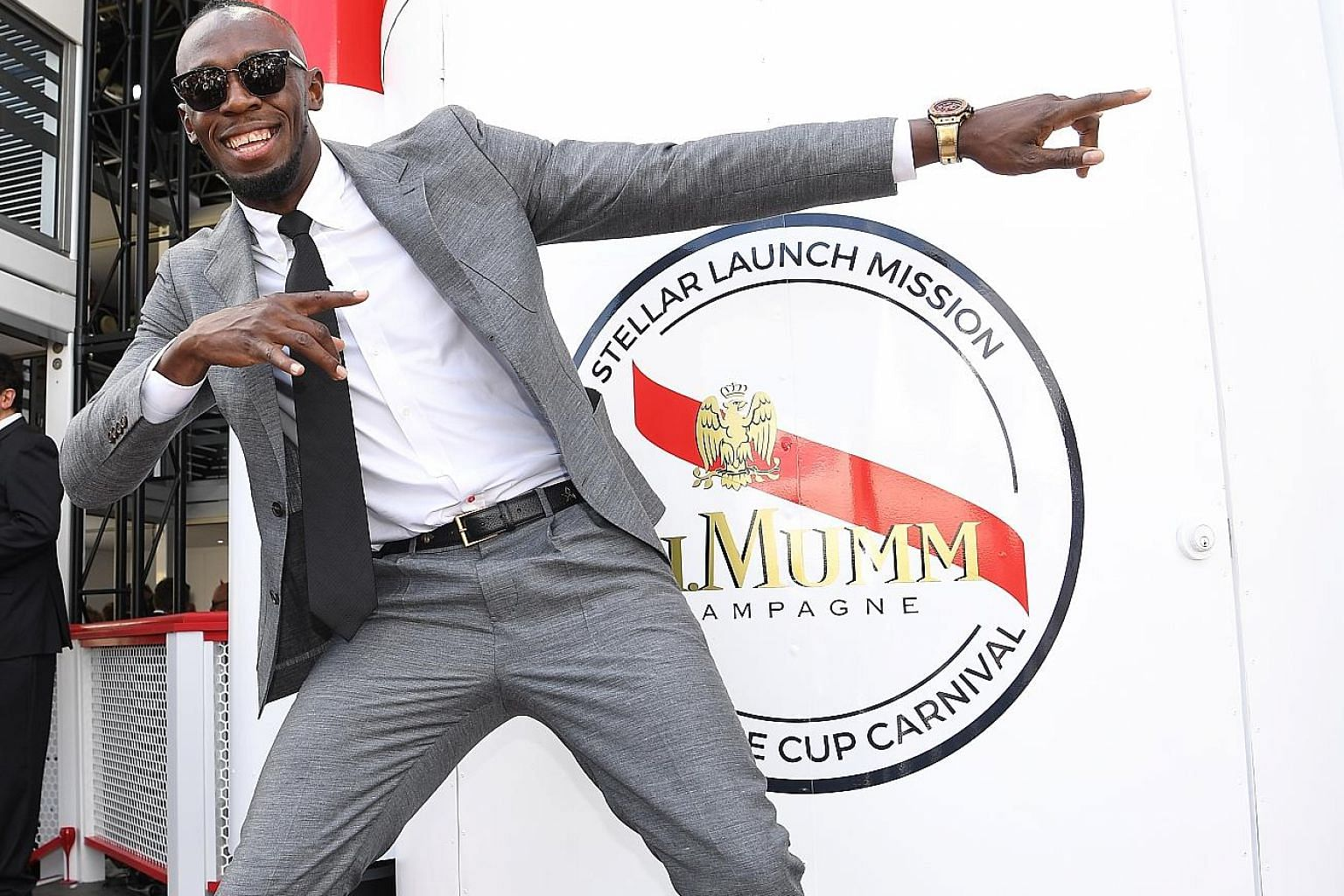 Usain Bolt striking a familiar pose at the Mumm marquee during the Victoria Derby Day, part of the Melbourne Cup Carnival, at Flemington Racecourse yesterday.