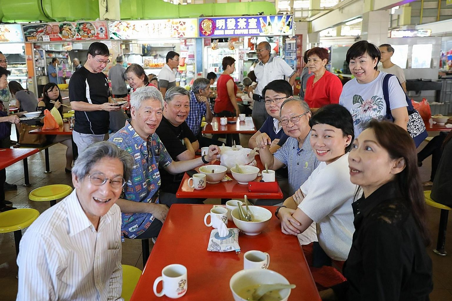 Dr Tan Cheng Bock (seated third from bottom right) and Mr Lee Hsien Yang (second from bottom left) having breakfast at West Coast Market and Food Centre yesterday.