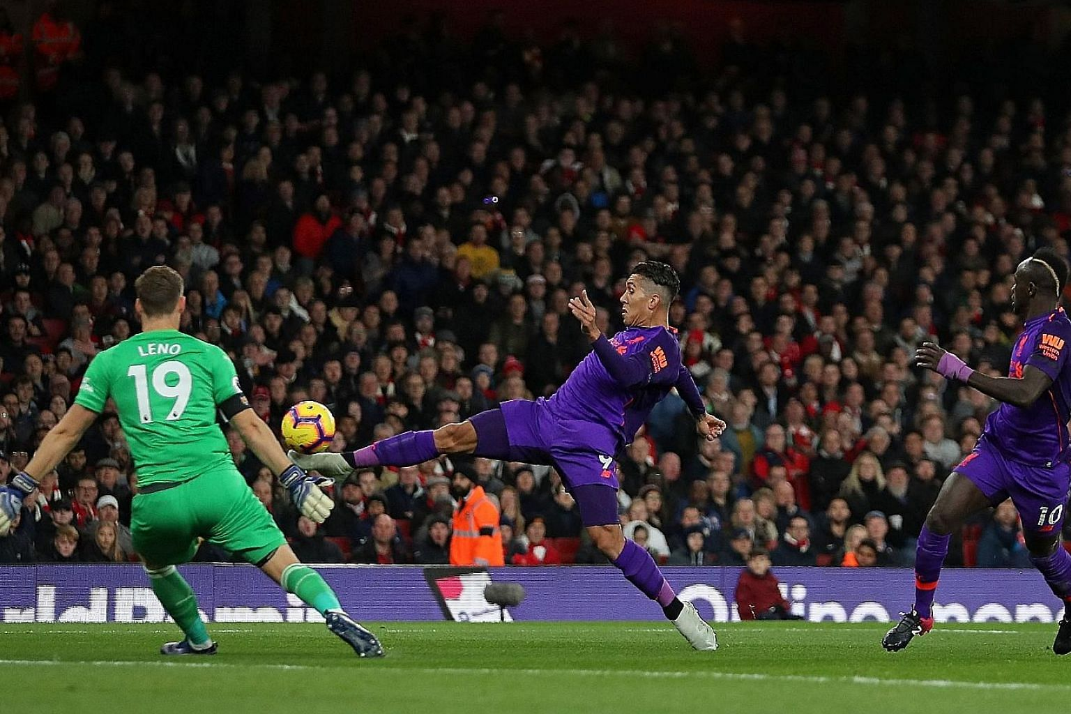 Liverpool's Roberto Firmino lifting a shot over Bernd Leno that beat the Arsenal goalkeeper but not the woodwork. The Brazilian's teammate Sadio Mane (No. 10) tapped home the rebound, only for the goal to be chalked off.
