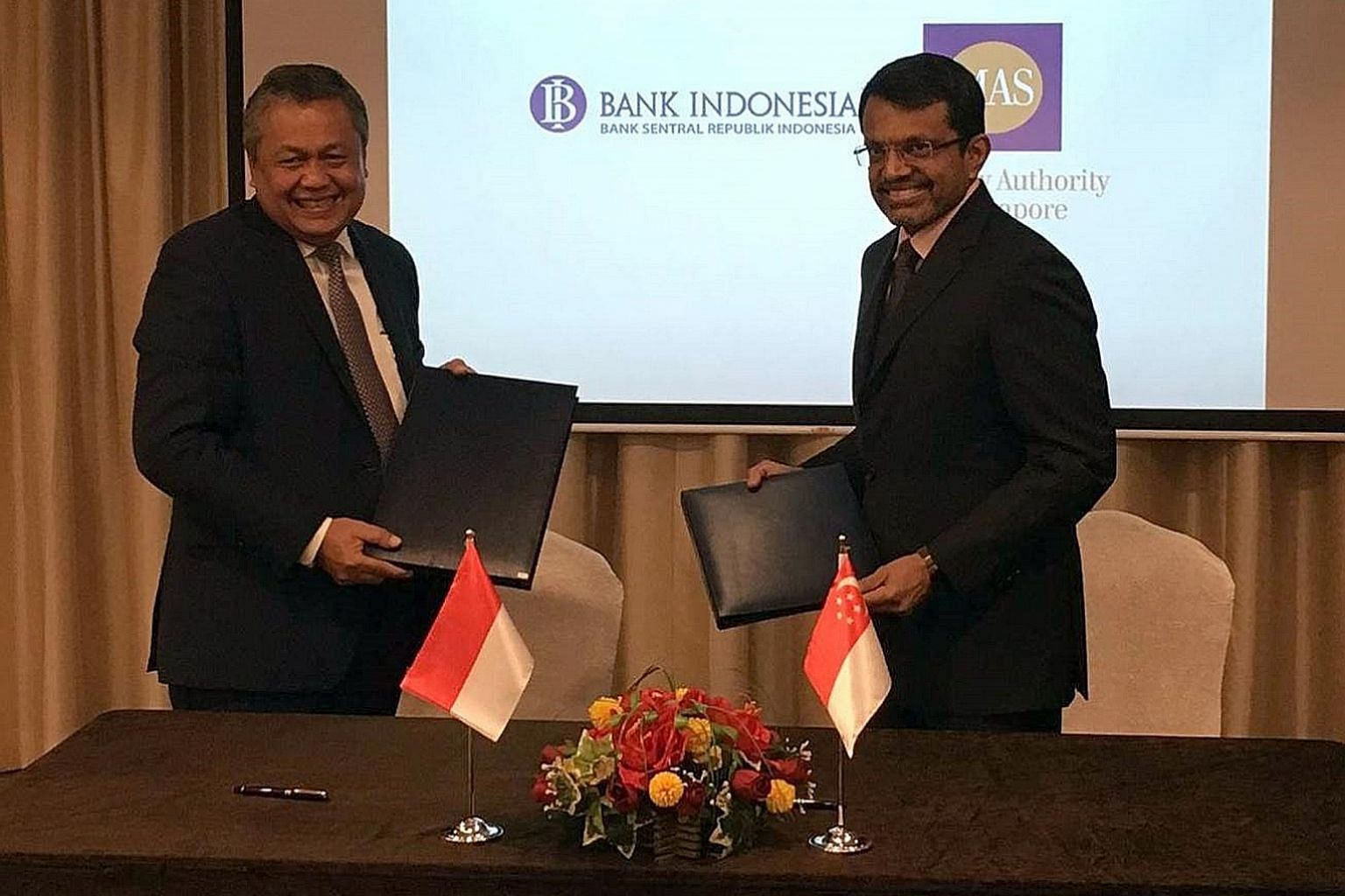 Bank Indonesia governor Perry Warjiyo (left) and Monetary Authority of Singapore managing director Ravi Menon at yesterday's signing ceremony for the bilateral financial arrangement.
