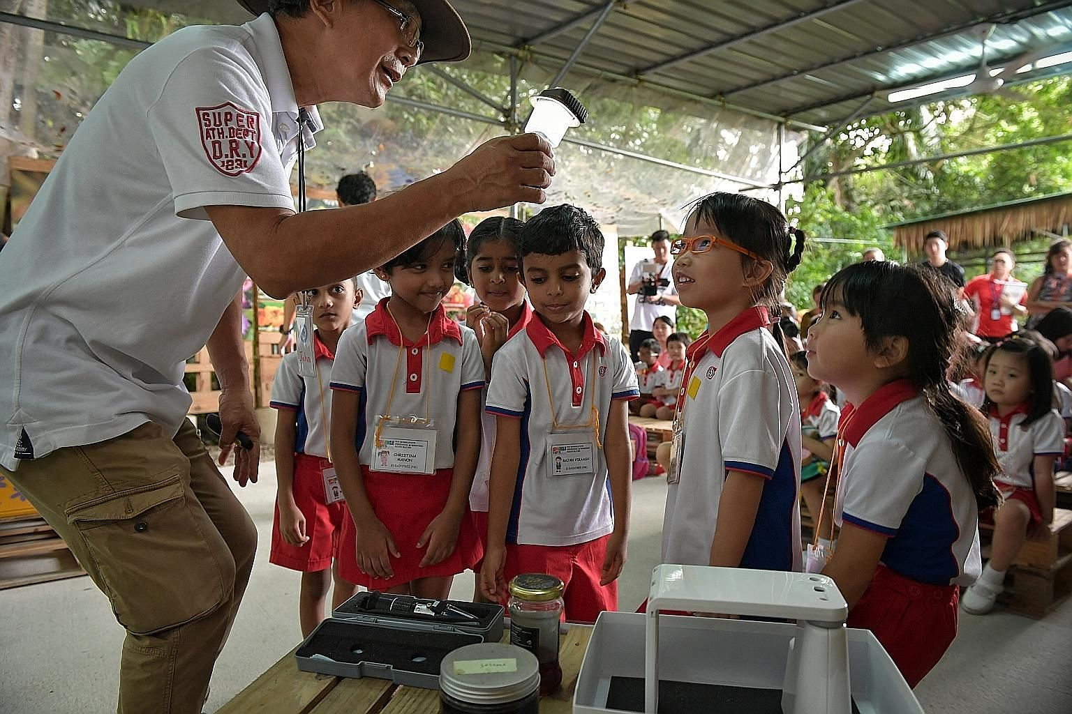 Bee Amazed Garden founder John Chong Chin Hong showing PCF Sparkletots pre-schoolers who visited his bee farm yesterday how honey is made. PCF Sparkletots has started an outdoor education programme for about 6,000 children from 73 centres for the sch