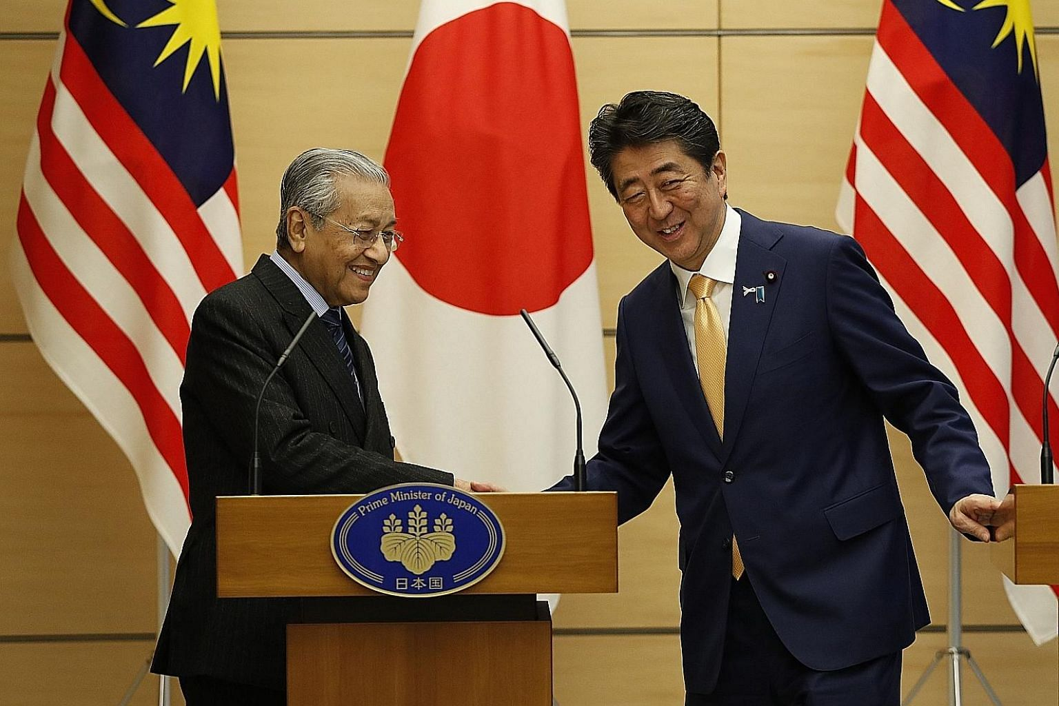 Malaysian Prime Minister Mahathir Mohamad exchanging greetings with Japanese Premier Shinzo Abe at the end of their joint news conference at Mr Abe's official residence in Tokyo yesterday.