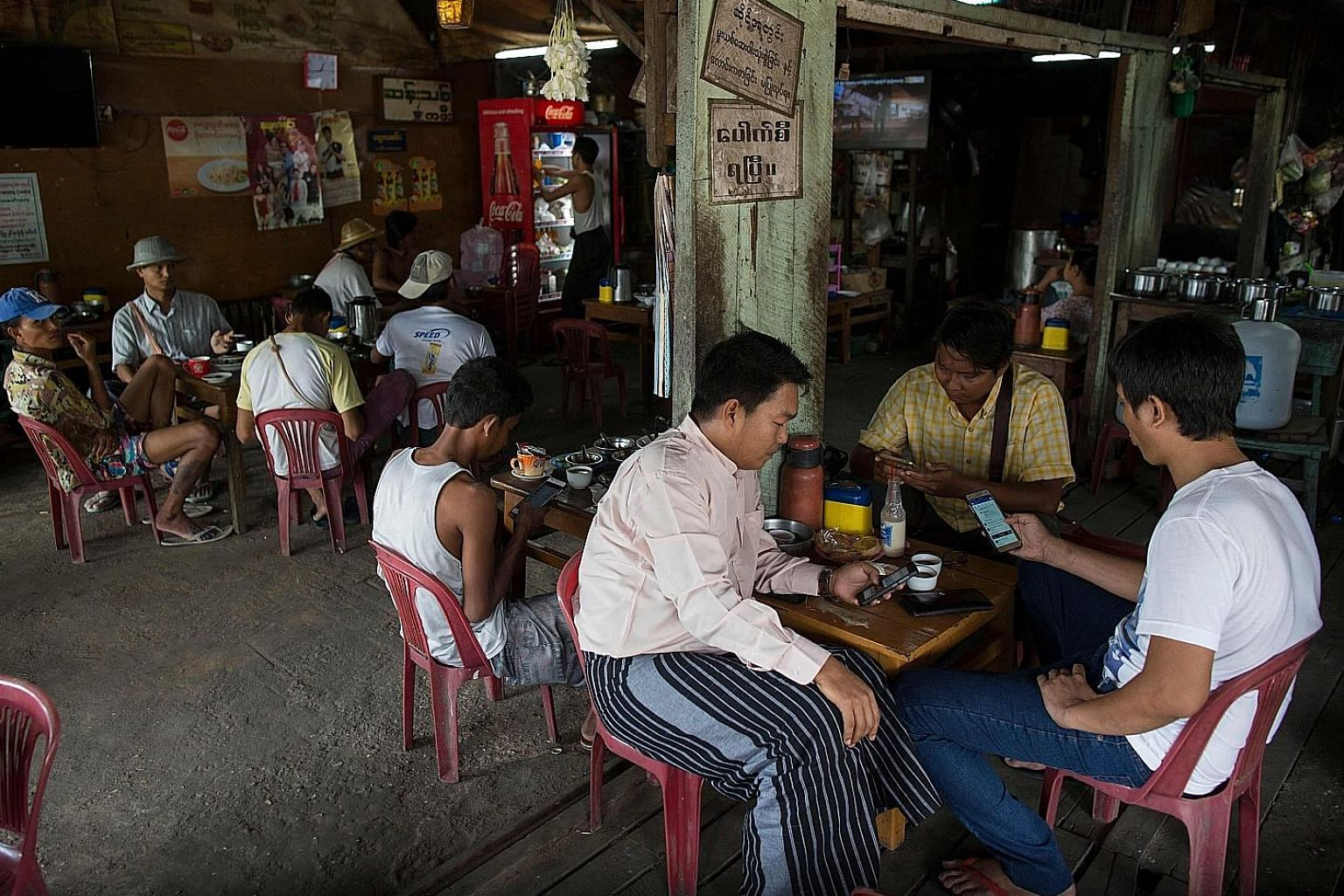 People using their mobile phones to access Facebook. The company has a team to work on Myanmar-specific issues, and has employed 99 native Myanmar-language speakers to review content, said product policy manager Alex Warofka in a blog post.