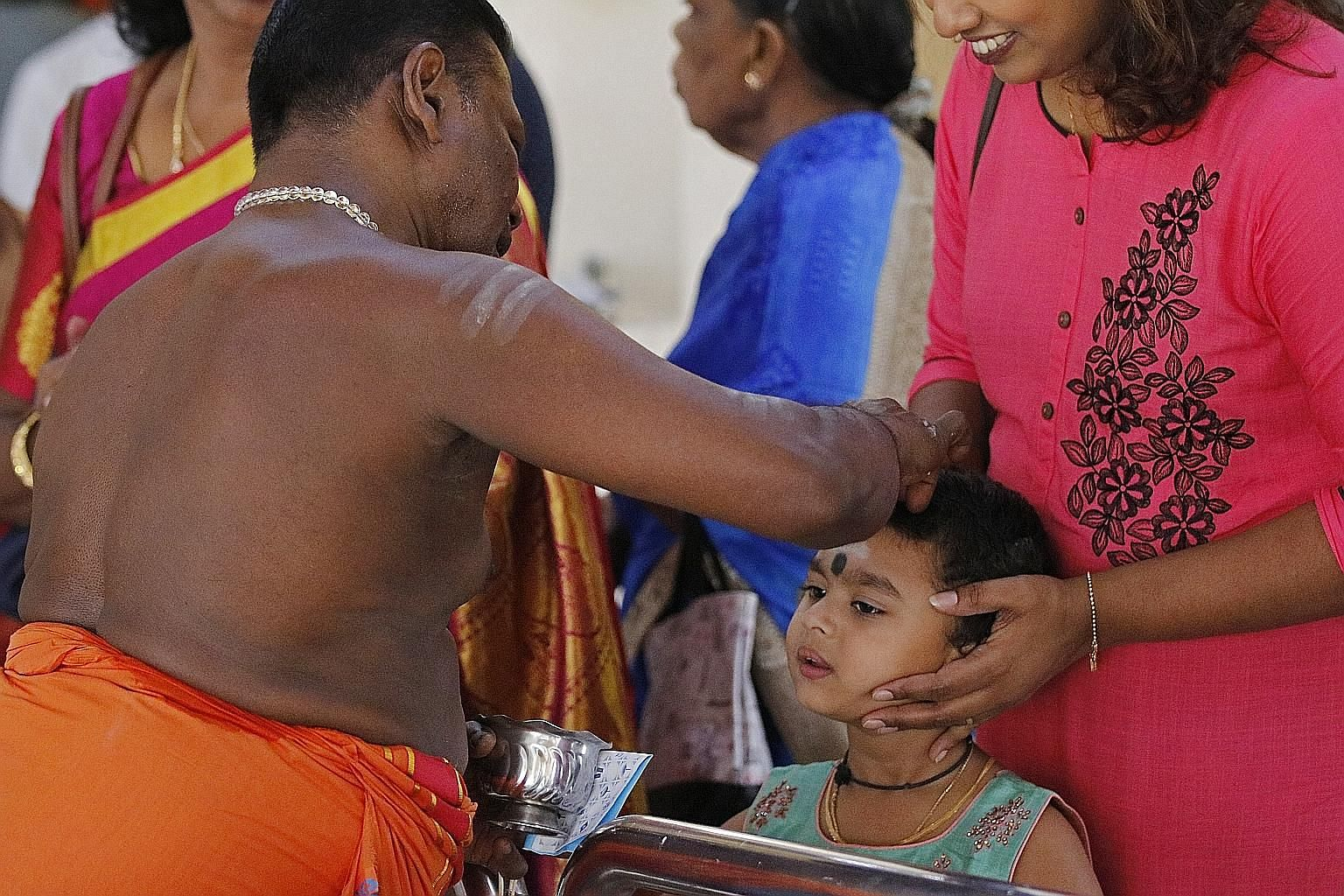 The chief priest of Sri Mariamman Temple applying holy ash on a child's forehead yesterday morning as part of a ritual. Migrant workers watching a Spanish dance performance at a concert organised by the Little India Shopkeepers and Heritage Associati