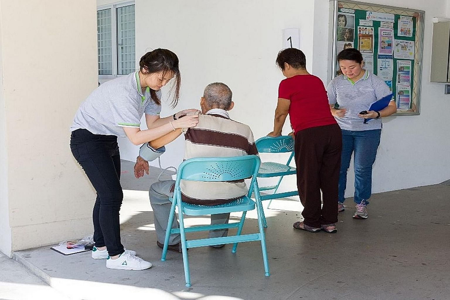 Staff from the Geriatric Education and Research Institute conduct blood pressure checks prior to carrying out a simple exercise session for older adults.