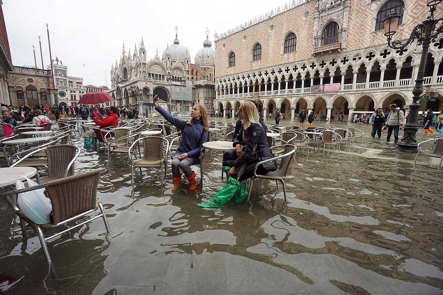 Tourists posing for a selfie in the flooded St Mark's Square in Venice last Thursday.
