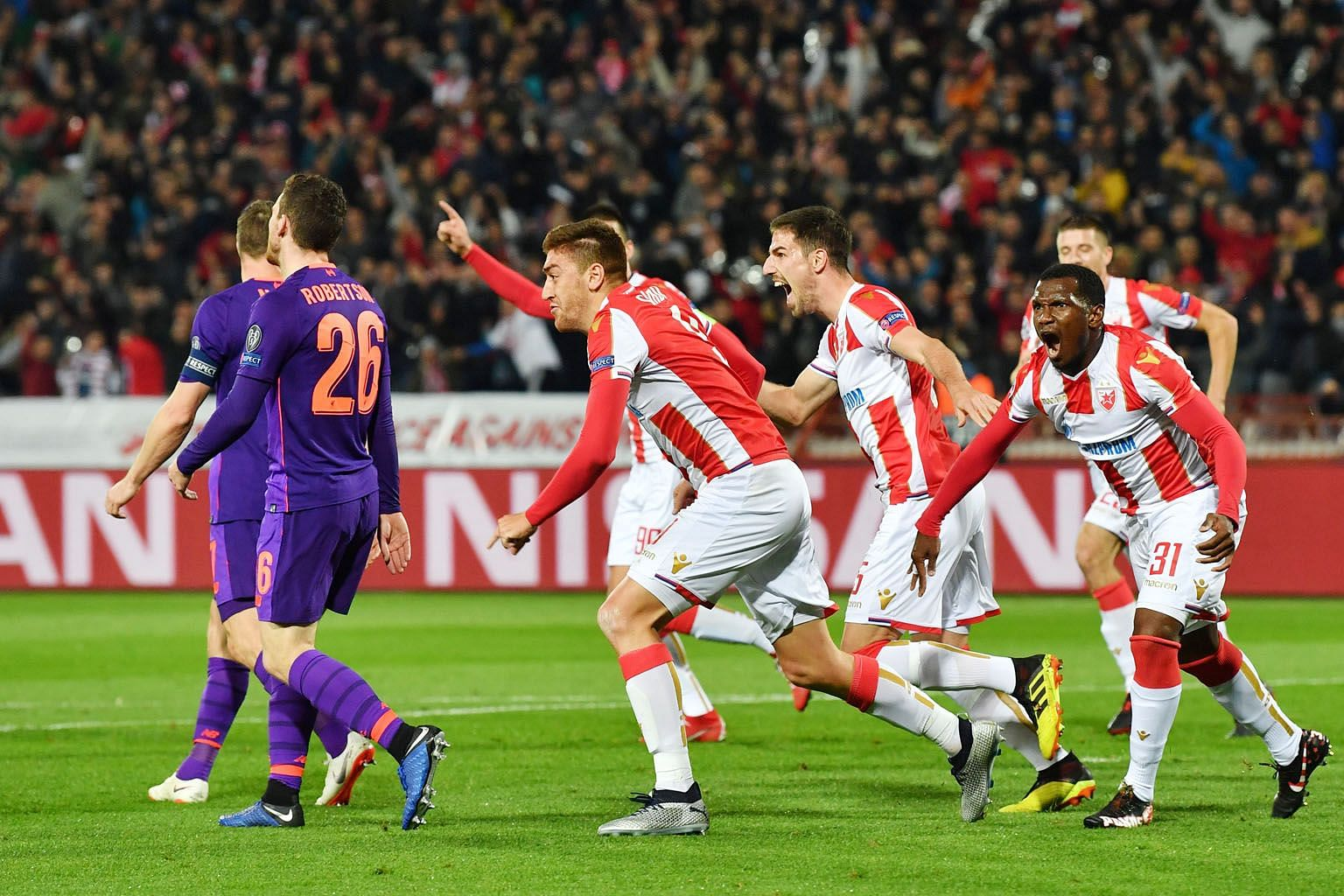 Red Star Belgrade's Milan Pavkov (centre) celebrates his first goal against Liverpool after heading home from a corner. He later doubled his tally as the Serbian champions recorded their first Champions League win this season.