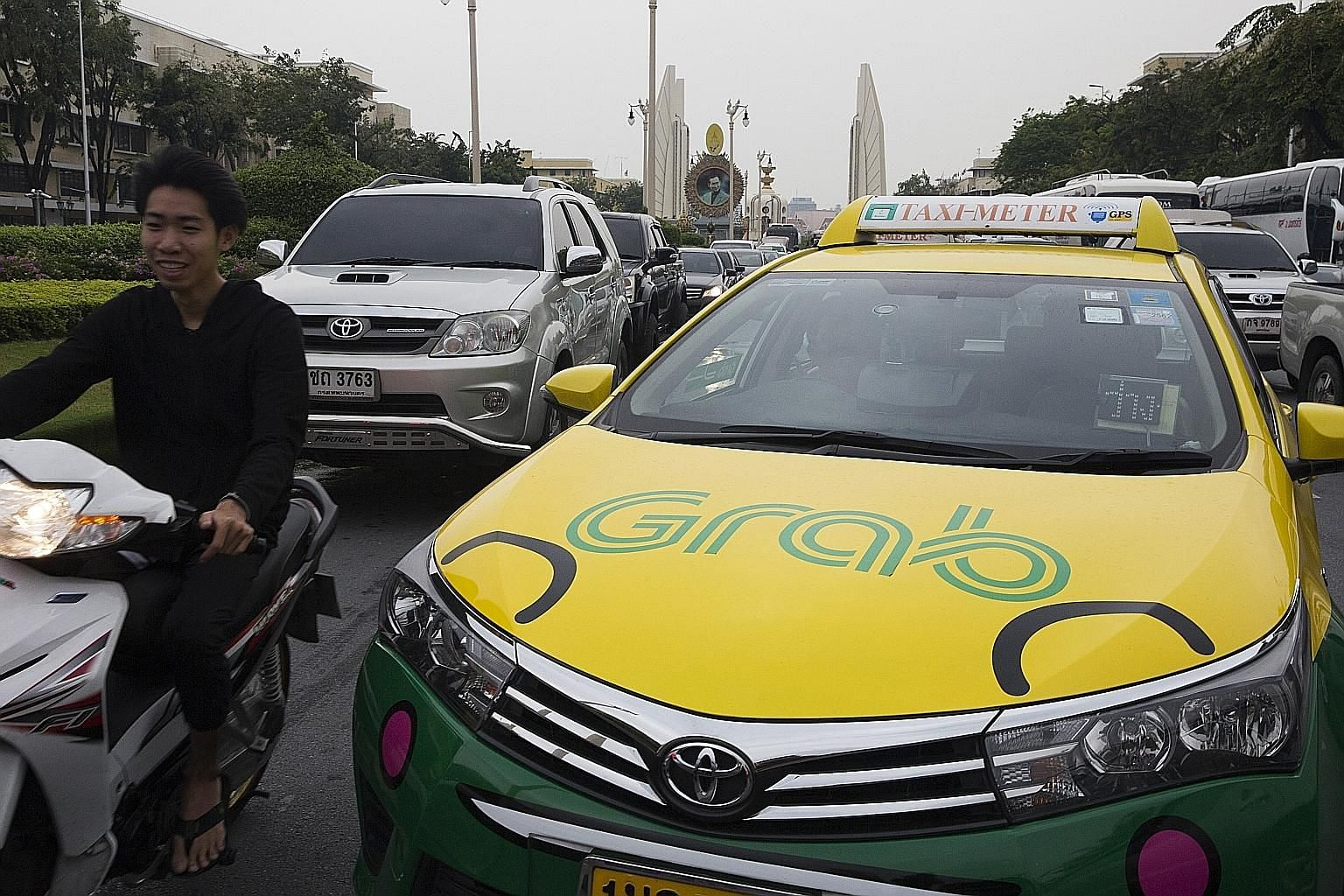 The Grab logo displayed on a taxi in Bangkok. The ride-hailing firm and Kasikornbank are in a mobile payment venture which could start operations early next year.
