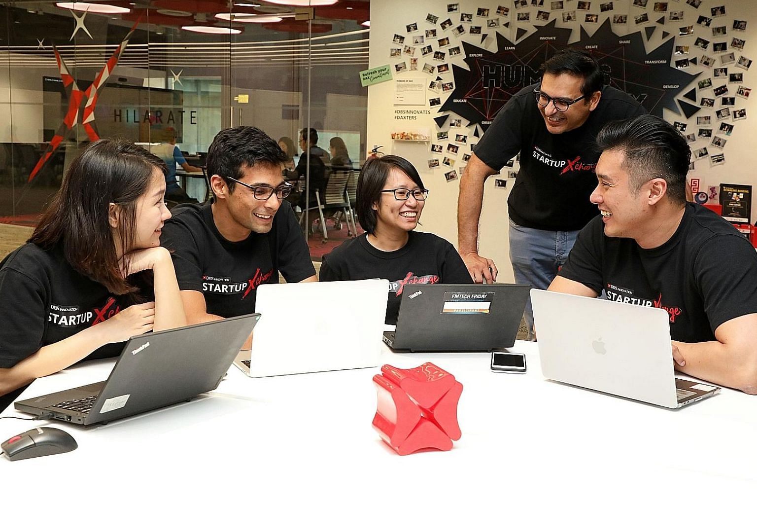 "Impress.AI chief executive officer and co-founder Sudhanshu Ahuja (second from left) with DBS staff, including Mr Bidyut Dumra (second from right), the bank's head of Innovation. Impress.AI worked with DBS to come up with Jim, an acronym for ""Jobs In"