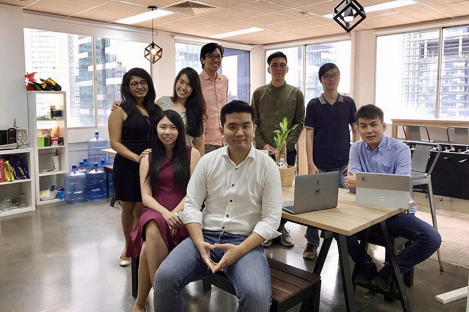 Mr Wong Hong Ting (in white), founder of artificial intelligence firm Botbot.ai, with his team. He says data-driven firms like his will face far greater technical challenges if the free flow of data across borders is restricted.