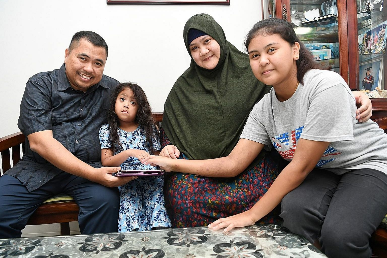 Mr Elfian Harun and his wife, Madam Salinah Parsiri, with their adopted child, five-year-old Anis Humairah, and birth daughter, 17-year-old Anis Amirah. The couple adopted Humairah when she was two, and are also foster parents to four other children,