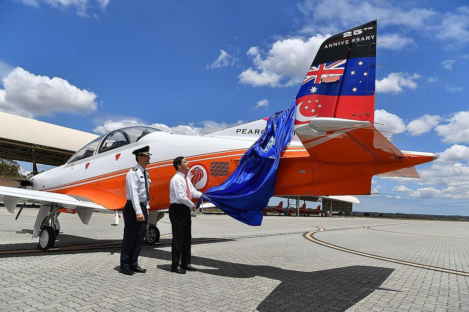 Senior Minister of State for Defence Heng Chee How unveiling the commemorative tail flash on a PC-21 plane at RSAF's 25th anniversary celebration of its training at Base Pearce in Australia yesterday, as commander of the RSAF's Air Force Training Com