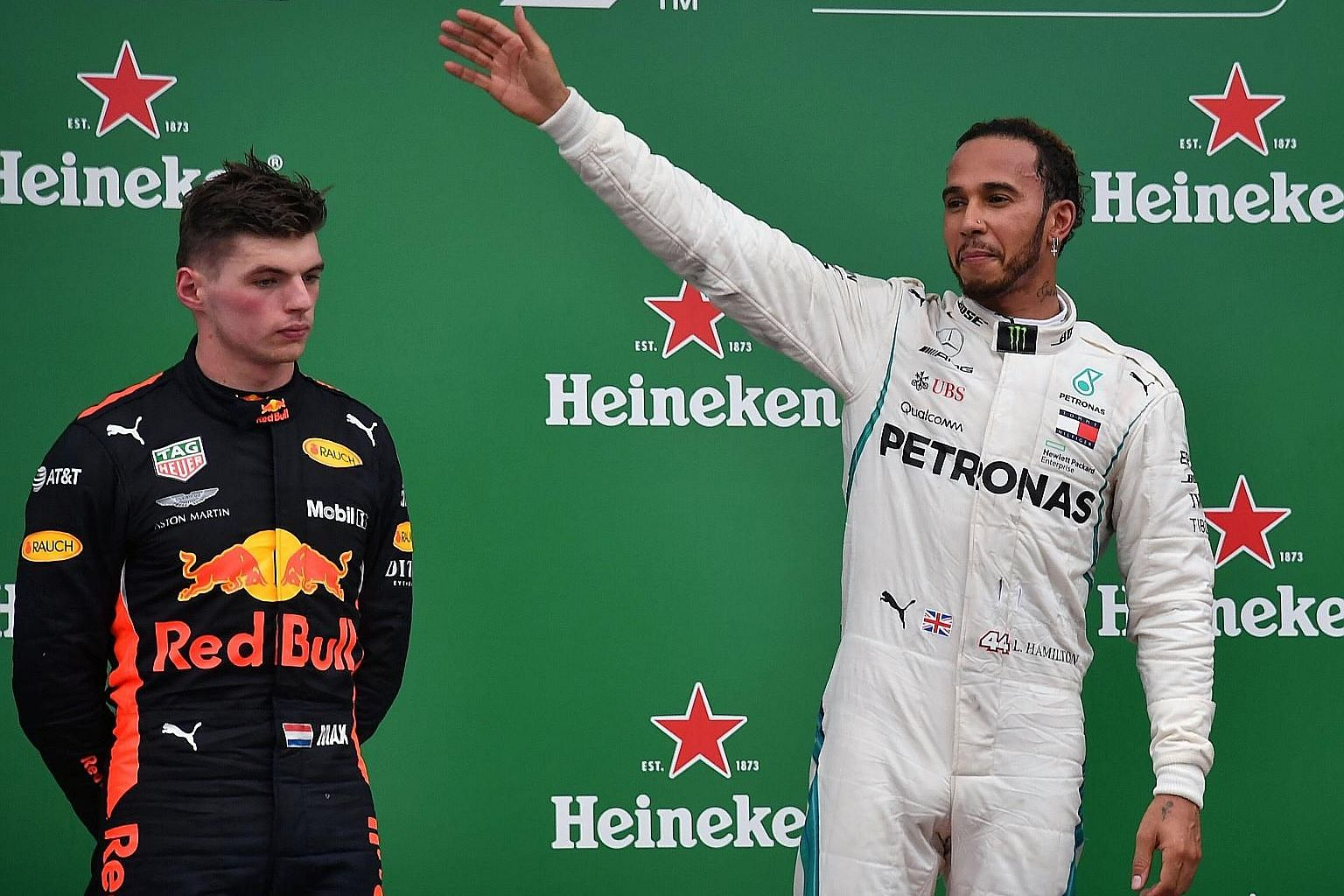 Lewis Hamilton celebrates his 10th victory of the season while Max Verstappen can only look on. The Red Bull driver's opportunity of winning back-to-back grands prix was quashed when a collision with Force India's Esteban Ocon on Lap 44 cost him the