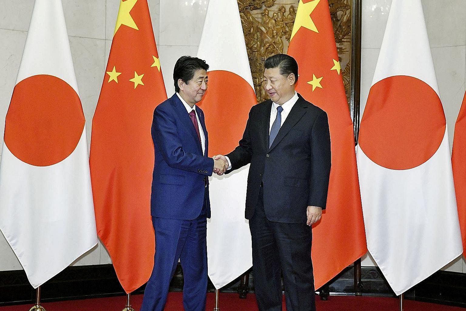 "Japanese Prime Minister Shinzo Abe (left) and Chinese President Xi Jinping during a meeting in Beijing on Oct 26. Mr Abe's ""cooperate but compete"" policy rides on the cross-currents of the present tensions; its success is similarly subject to the shi"