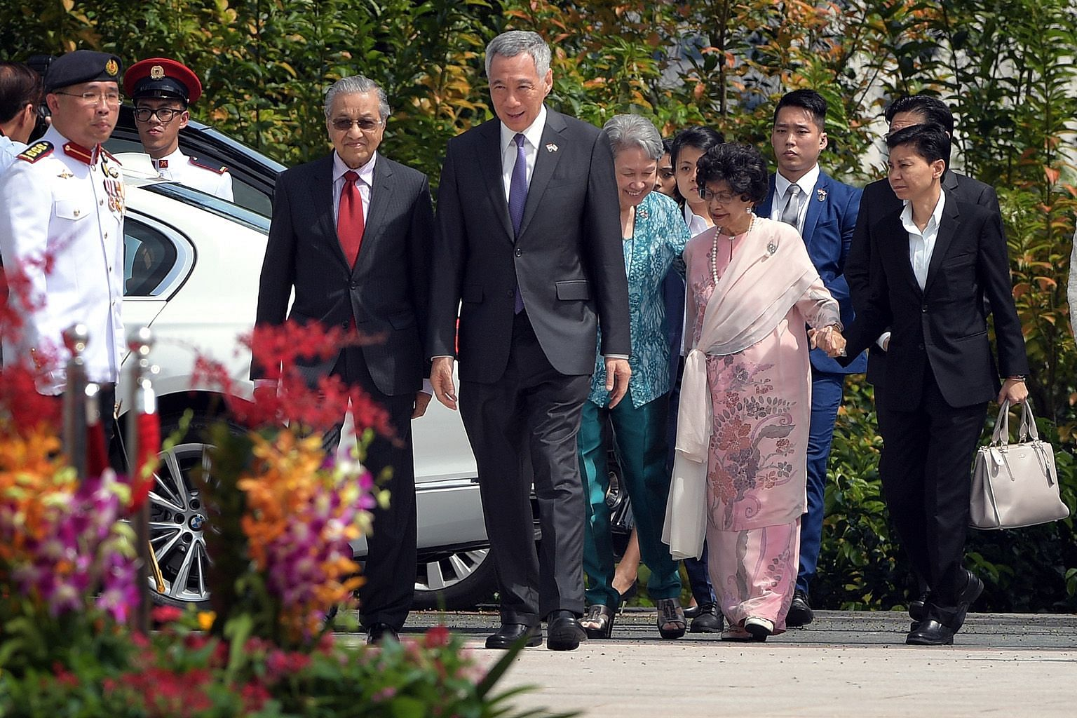 Malaysian Prime Minister Mahathir Mohamad and his wife Siti Hasmah Mohamad Ali being accompanied by Prime Minister Lee Hsien Loong and Mrs Lee on their arrival at the Istana yesterday.