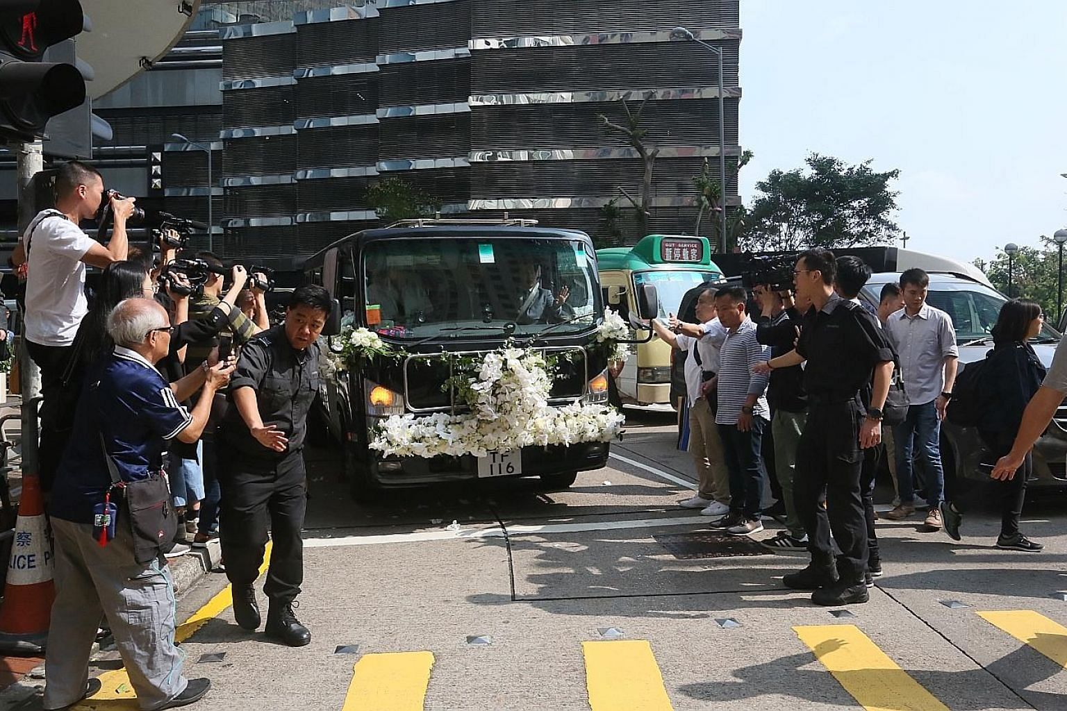 Left: Mr Louis Cha's son Andrew carrying his late father's photo into the hearse yesterday. Above: The hearse leaving the funeral parlour for Lantau island's Po Lin Monastery, where Mr Cha was cremated in a Buddhist ceremony. He died at the age of 94
