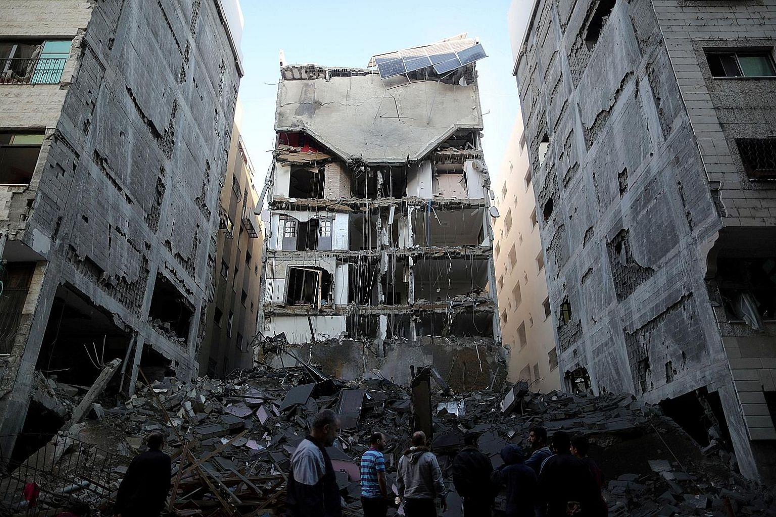 Palestinians gathering near the remains of a building that was completely destroyed by an Israeli air strike in Gaza. The fighting began after Israeli intelligence operatives inside the Gaza Strip were challenged by Hamas fighters.