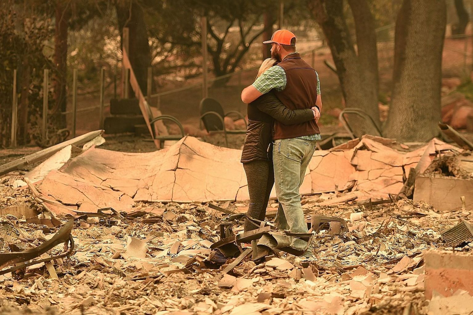 Mr and Mrs Chris Brown of the town of Paradise looking at the burnt remains of their house after wind-whipped flames tore through the region, leaving death and devastation in their wake.