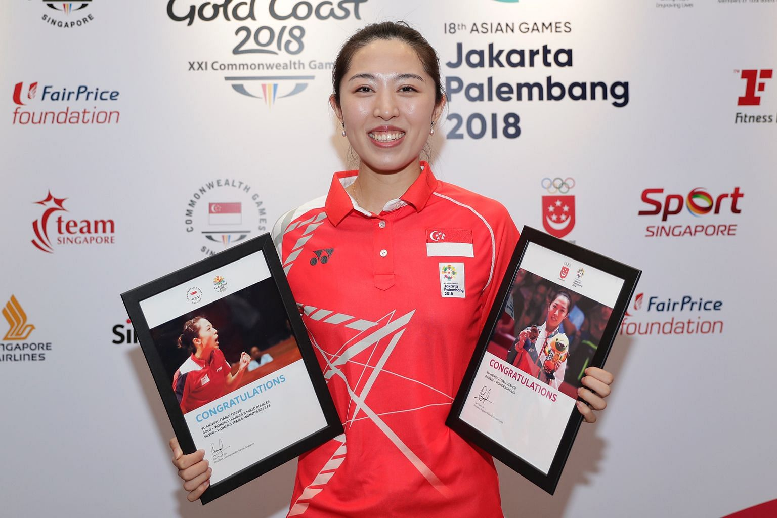 A happy Yu Mengyu holding mementoes of her showing at this year's Commonwealth and Asian Games.