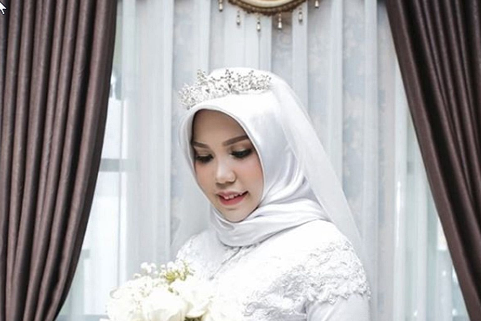 Photos of Ms Intan Syari wearing a white wedding dress and holding white roses went viral on social media in Indonesia.