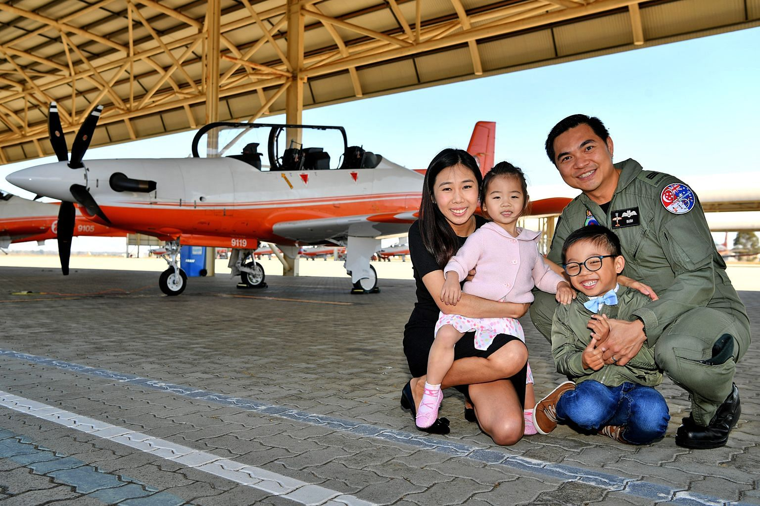 Captain Alvin Leow and his wife Mindy Poh with their daughter Reanne and son Reyes in Perth, Australia. In the background is the PC-21 aircraft.