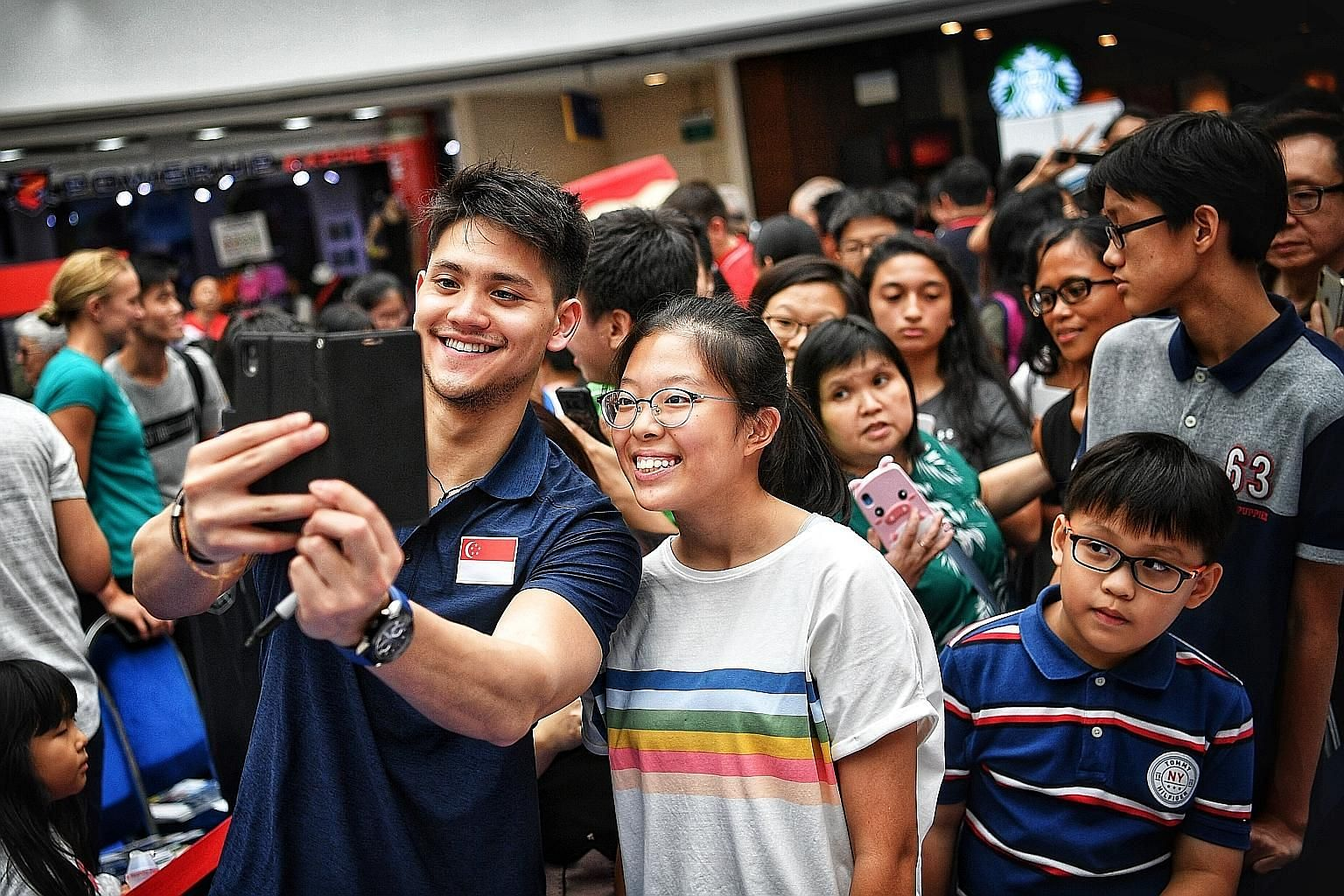 Olympic 100m butterfly gold medallist Joseph Schooling taking a wefie with a fan during the meet and greet session at Kallang Wave Mall yesterday, as other well-wishers wait in line.