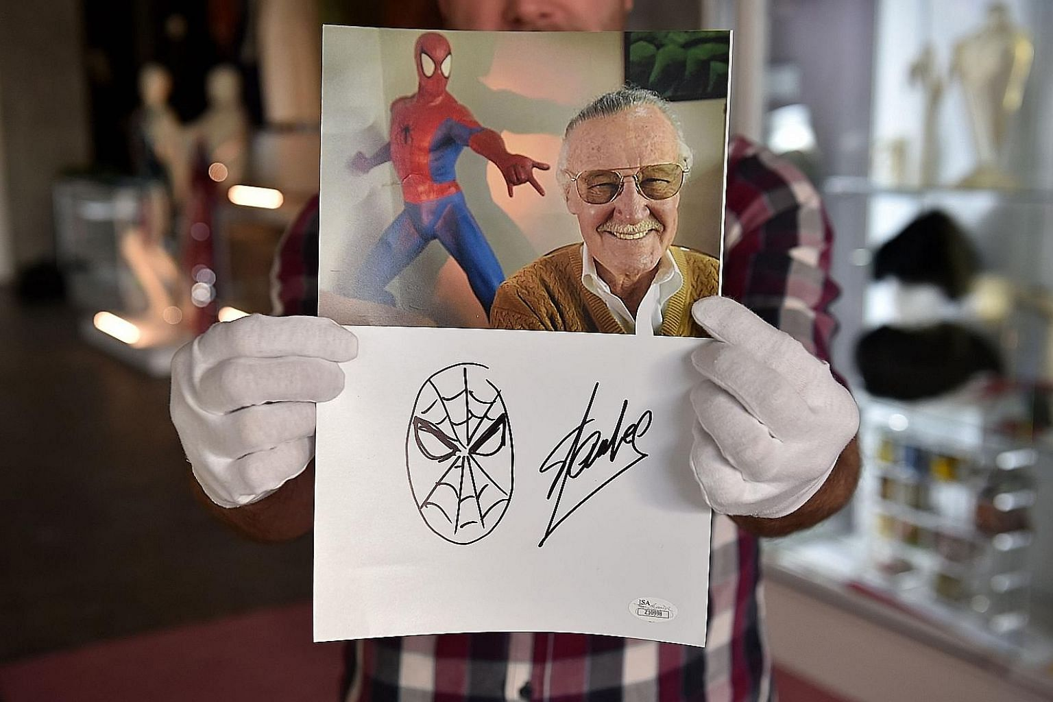 Many people, including this man dressed as Captain America, turned up at Stan Lee's Hollywood Walk of Fame star to pay tribute. An original sketch by Stan Lee of his most iconic creation, Spider-Man, beneath a portrait of Lee. The sketch is part of a