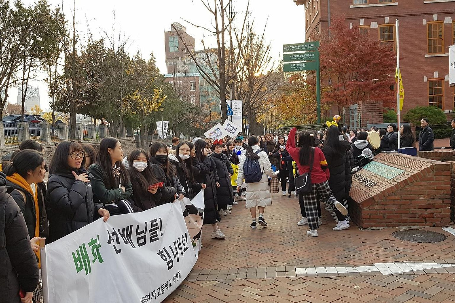 Students outside Ewha Girls' High School in Seoul to cheer on their seniors taking the exam, the culmination of 12 years of study in a highly competitive society. Good results are believed to open doors to prestigious universities and jobs.
