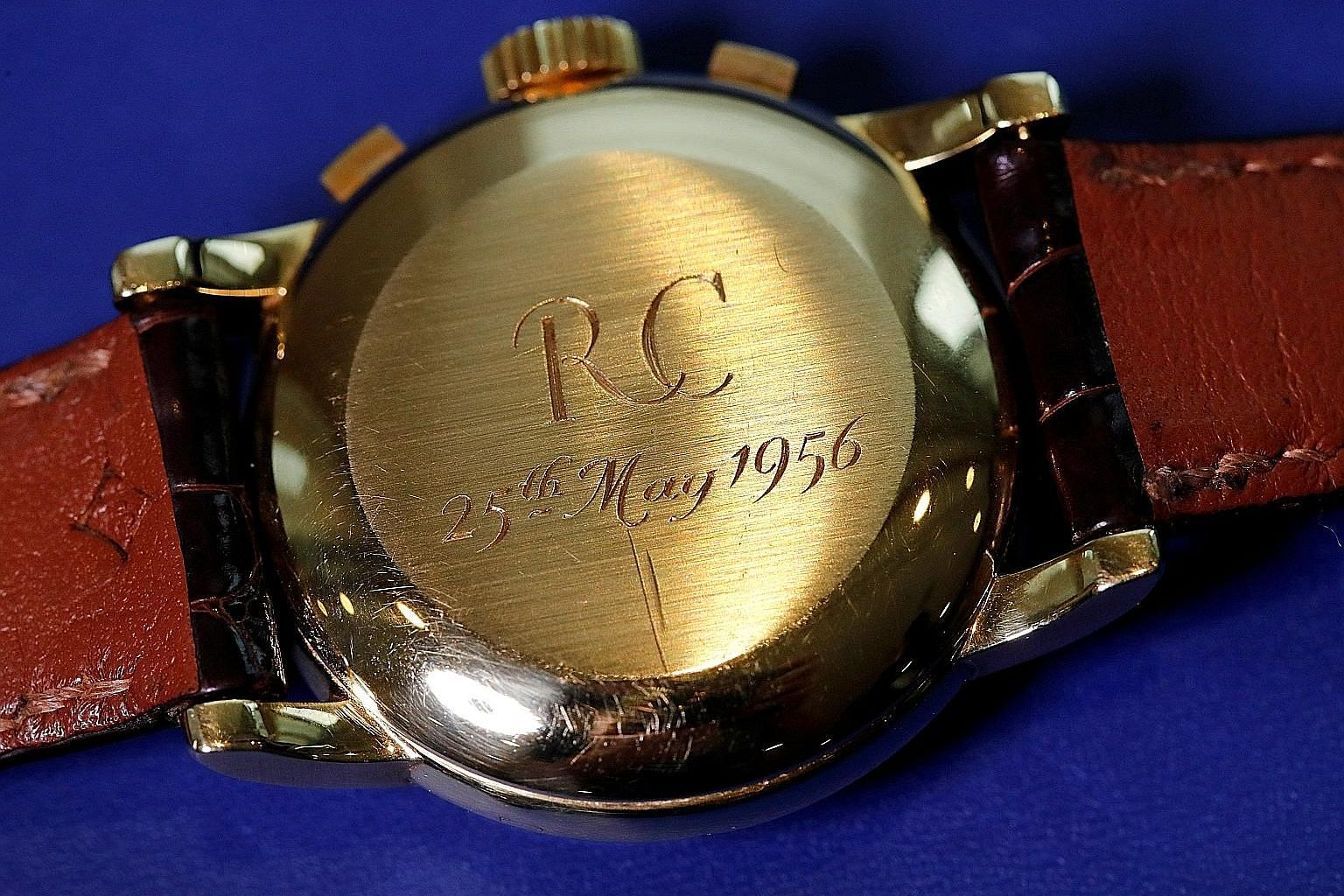 The watch (right) offers the day and date, a stopwatch and phases of the moon. The initials of the original owner, R.C., have been engraved on the back of the watch's yellow gold case (above).