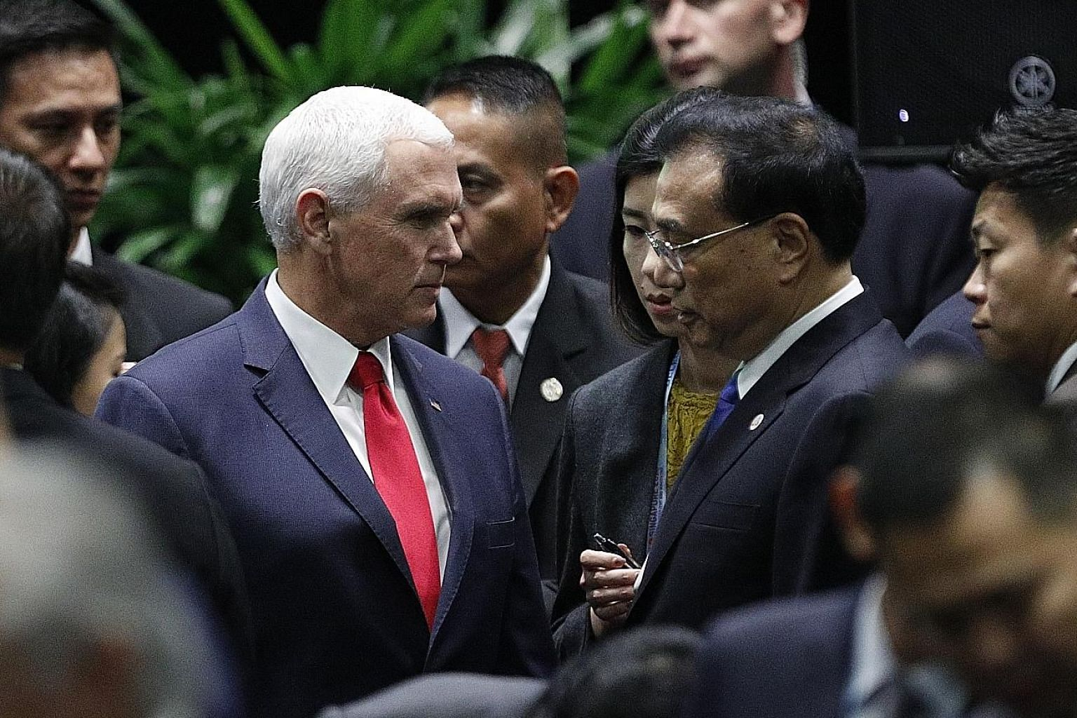 Above: US Vice-President Mike Pence and Chinese Premier Li Keqiang speaking to each other at the 13th East Asia Summit (EAS) yesterday. The US and China are in the midst of a trade war. Below: Russian President Vladimir Putin (left) speaking with Mr